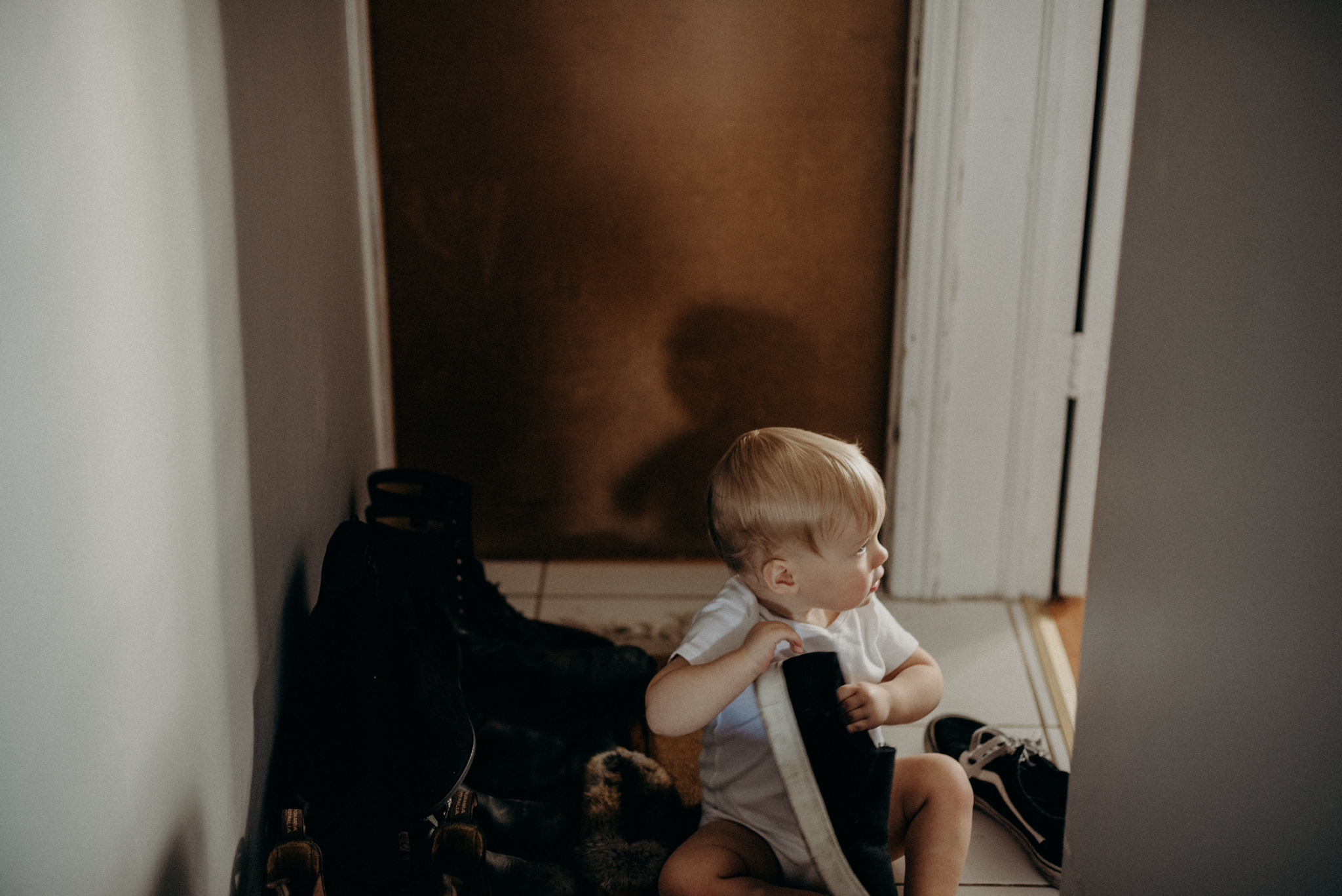 toddler playing with shoes in hallway