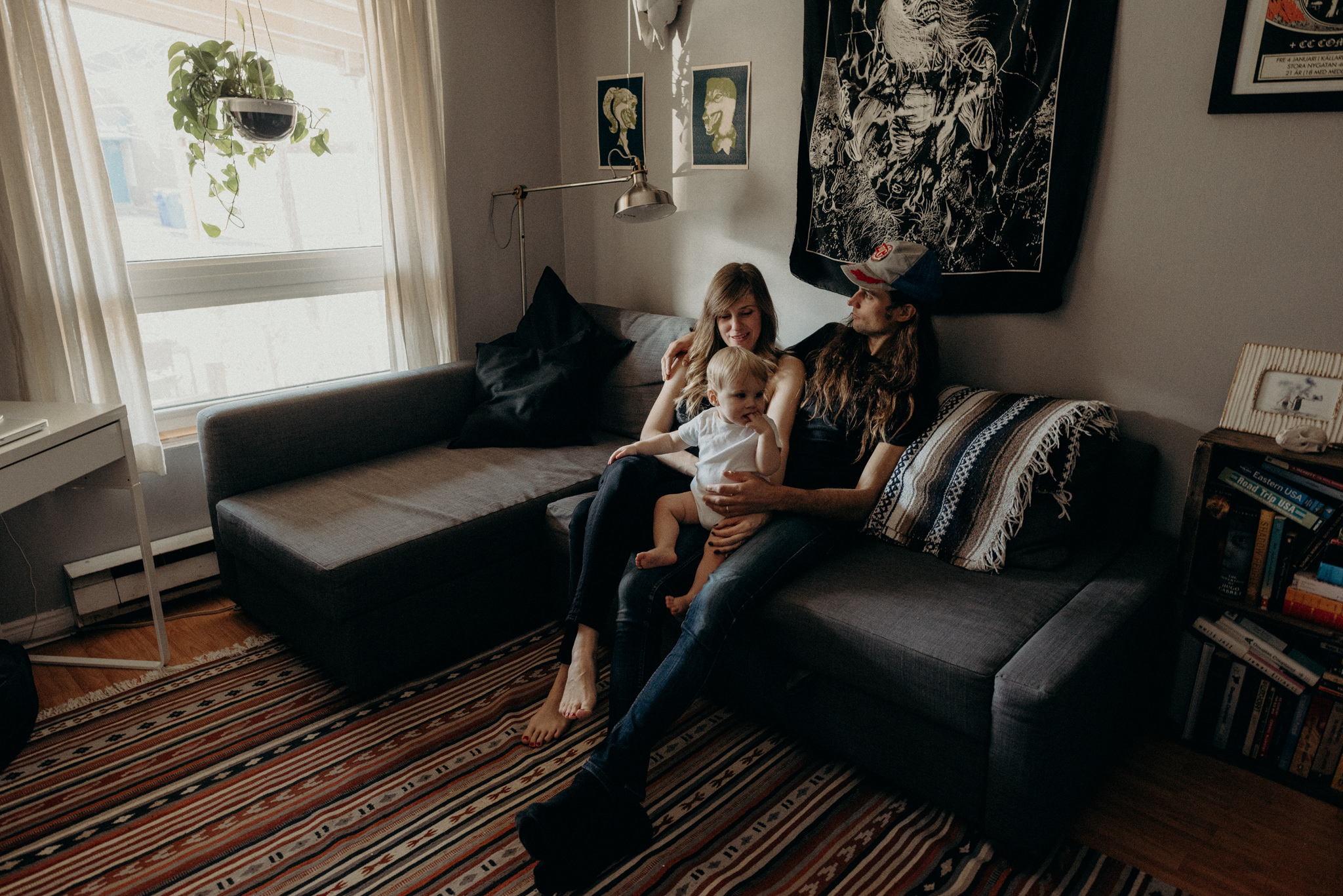 hip young couple sitting on couch in apartment with toddler