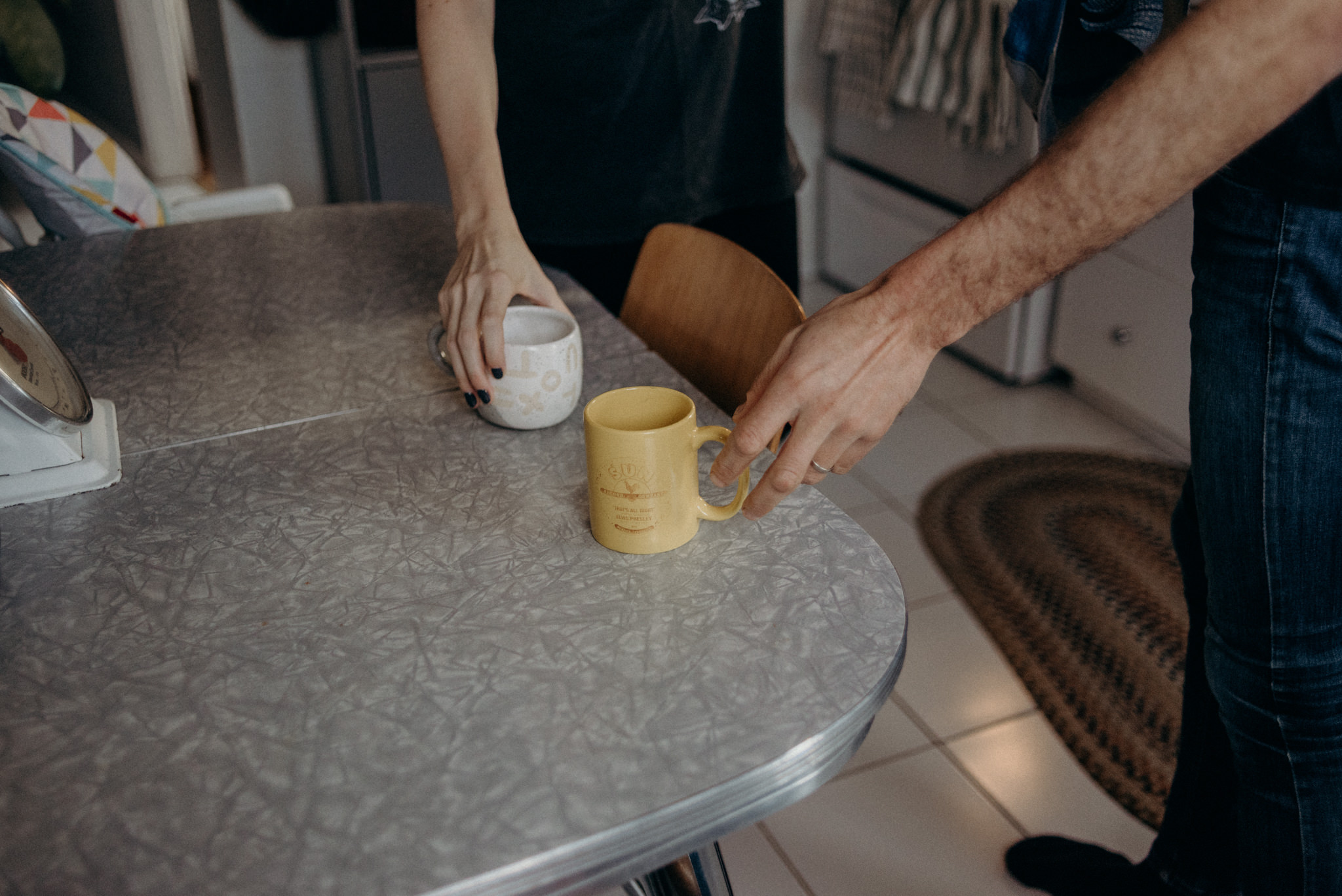 couple reaching for coffee mugs on table in kitchen