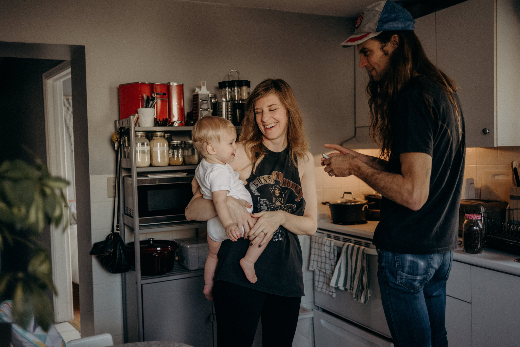 young couple with toddler in kitchen making coffee