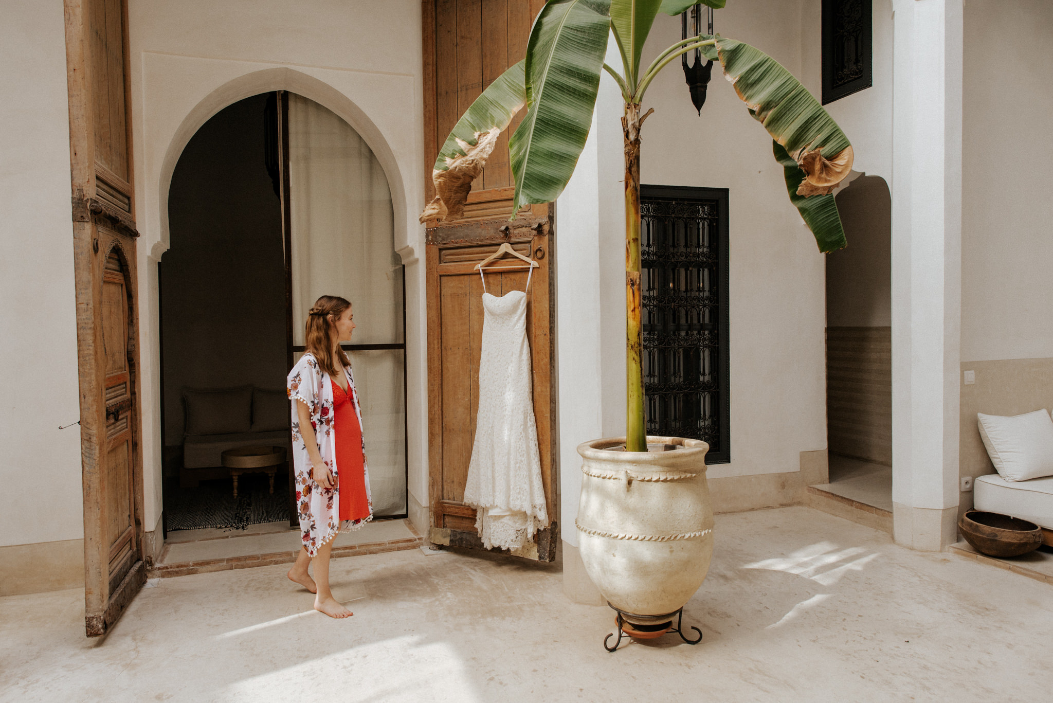 Bride and wedding dress hanging on door in Riad 42 for Morocco elopement