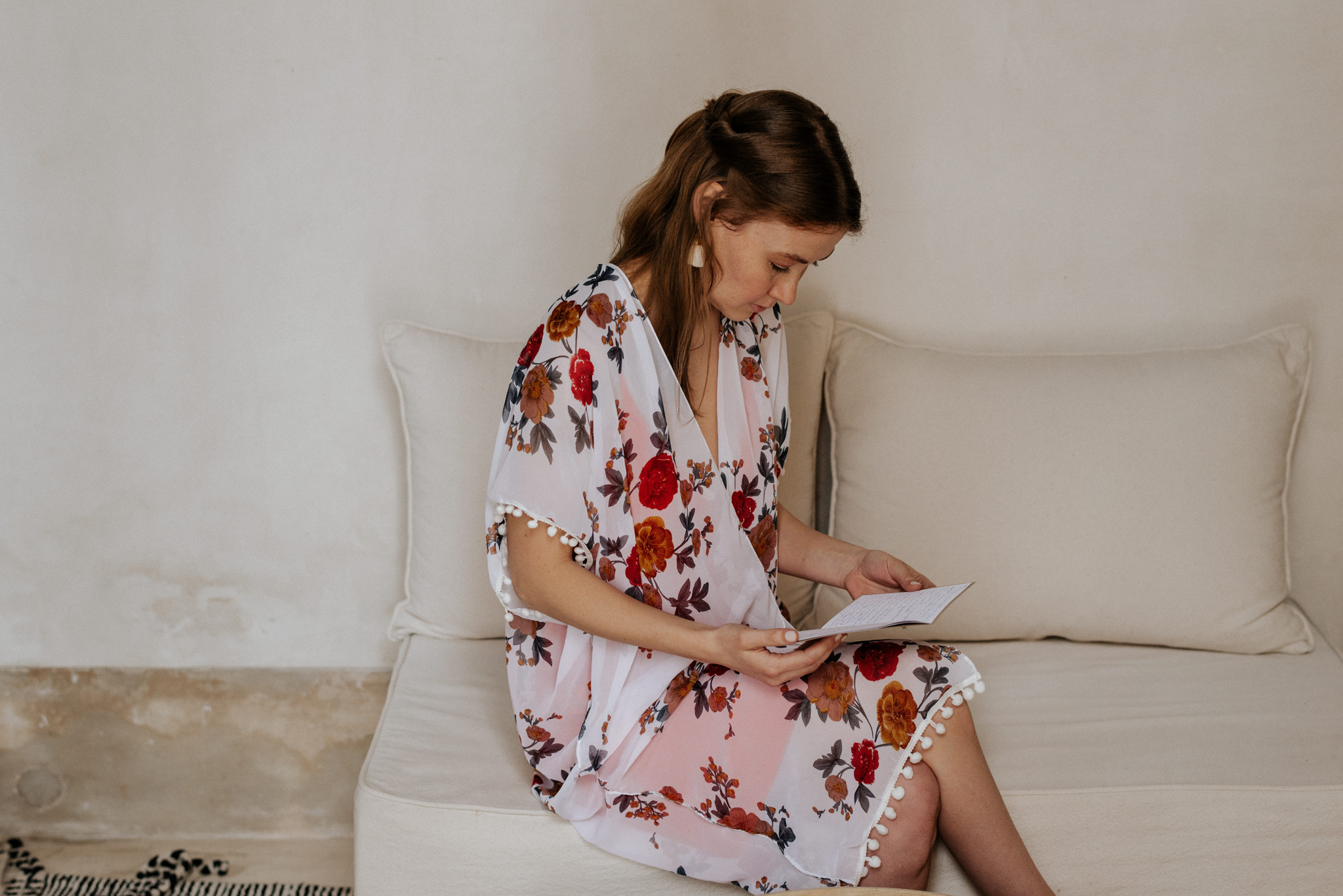 Bride in floral coverup reading vows before ceremony