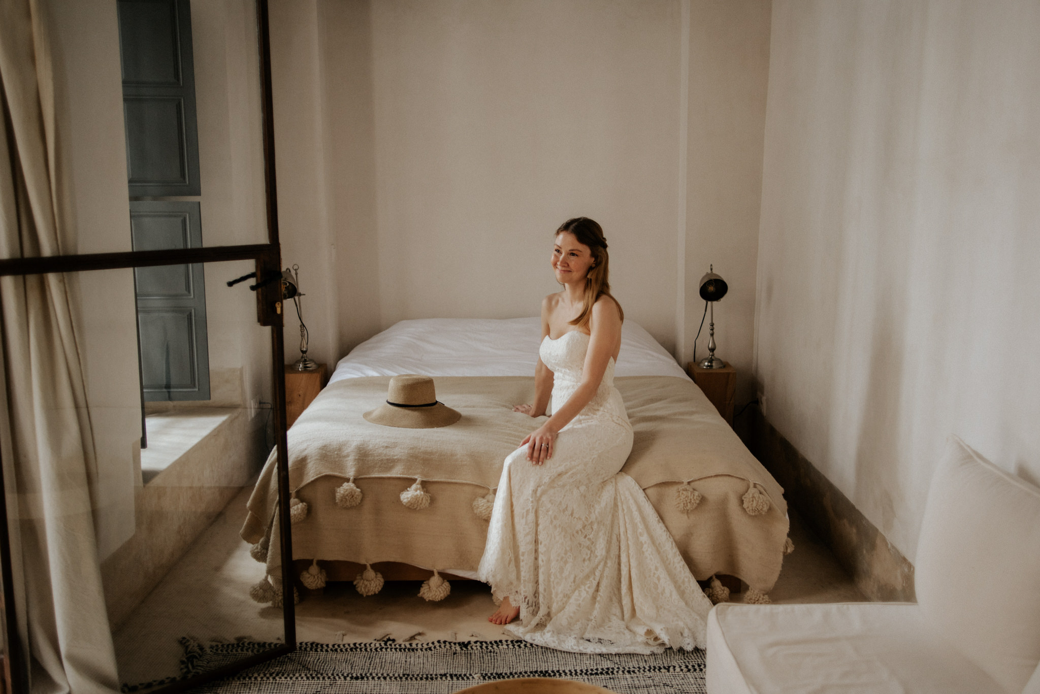 Bride sitting on bed in minimalist bedroom at Riad 42