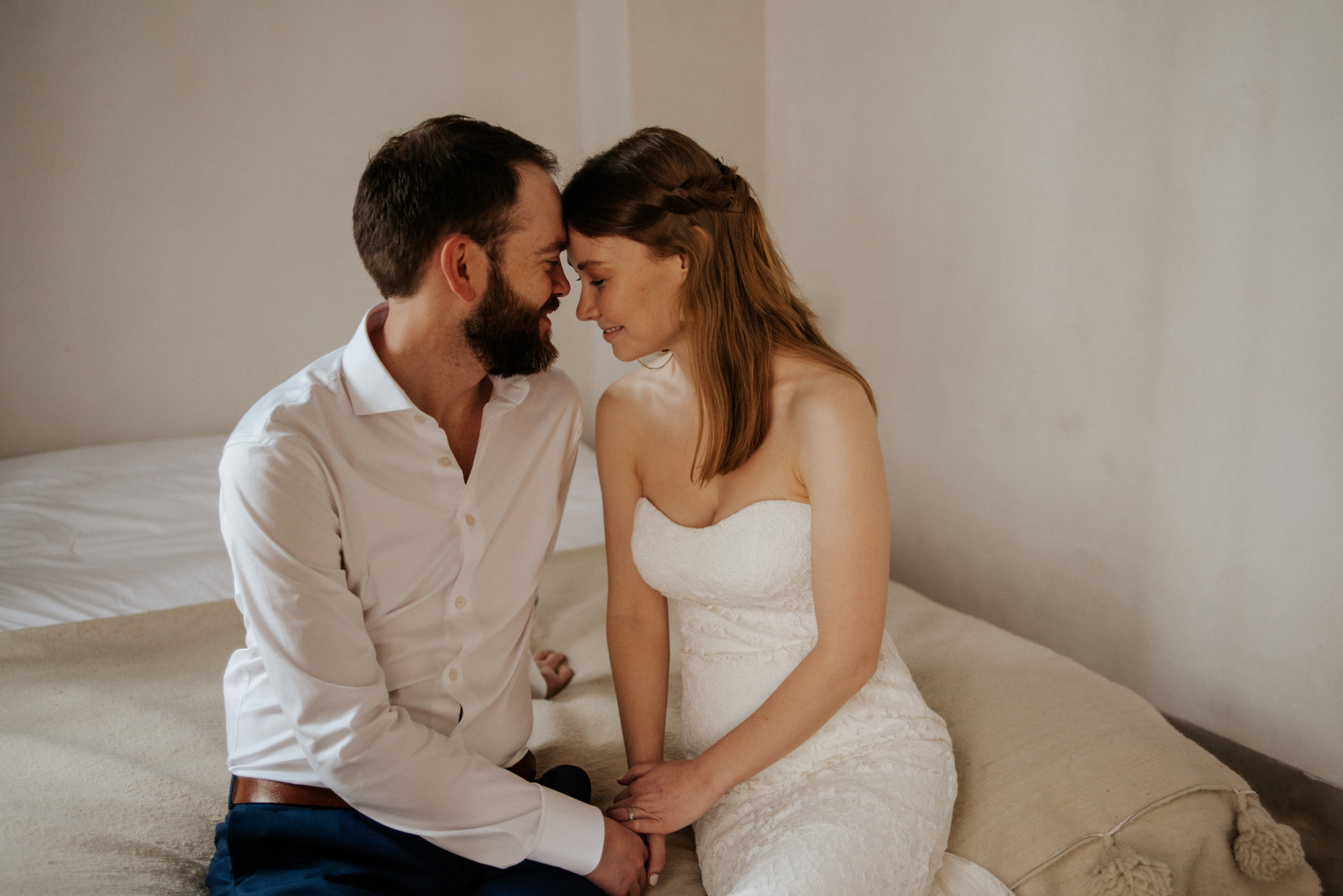 Bride and groom having a moment together sitting on bed before their elopement