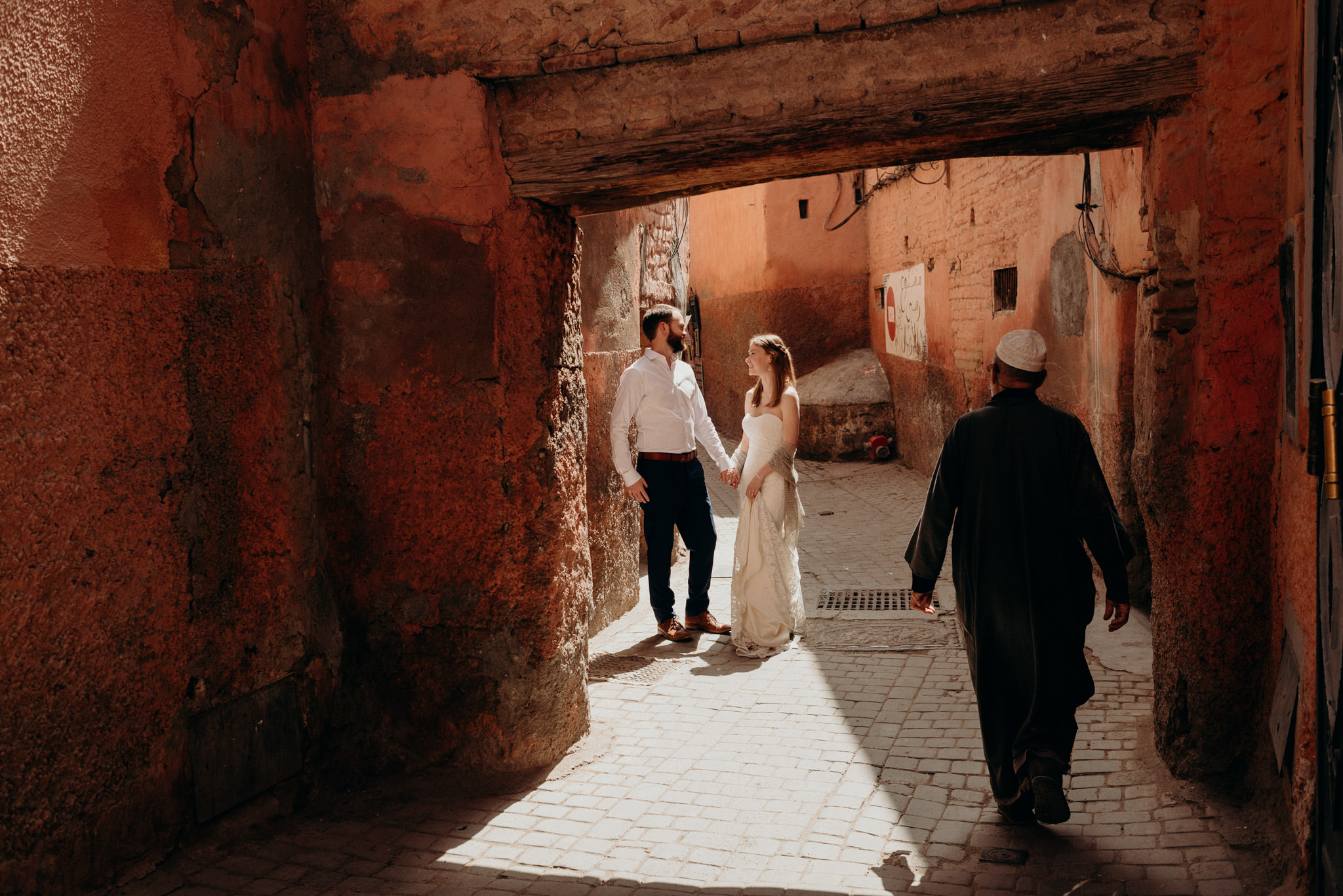 Bride and groom standing in light in the alleyways of the medina in Marrakech