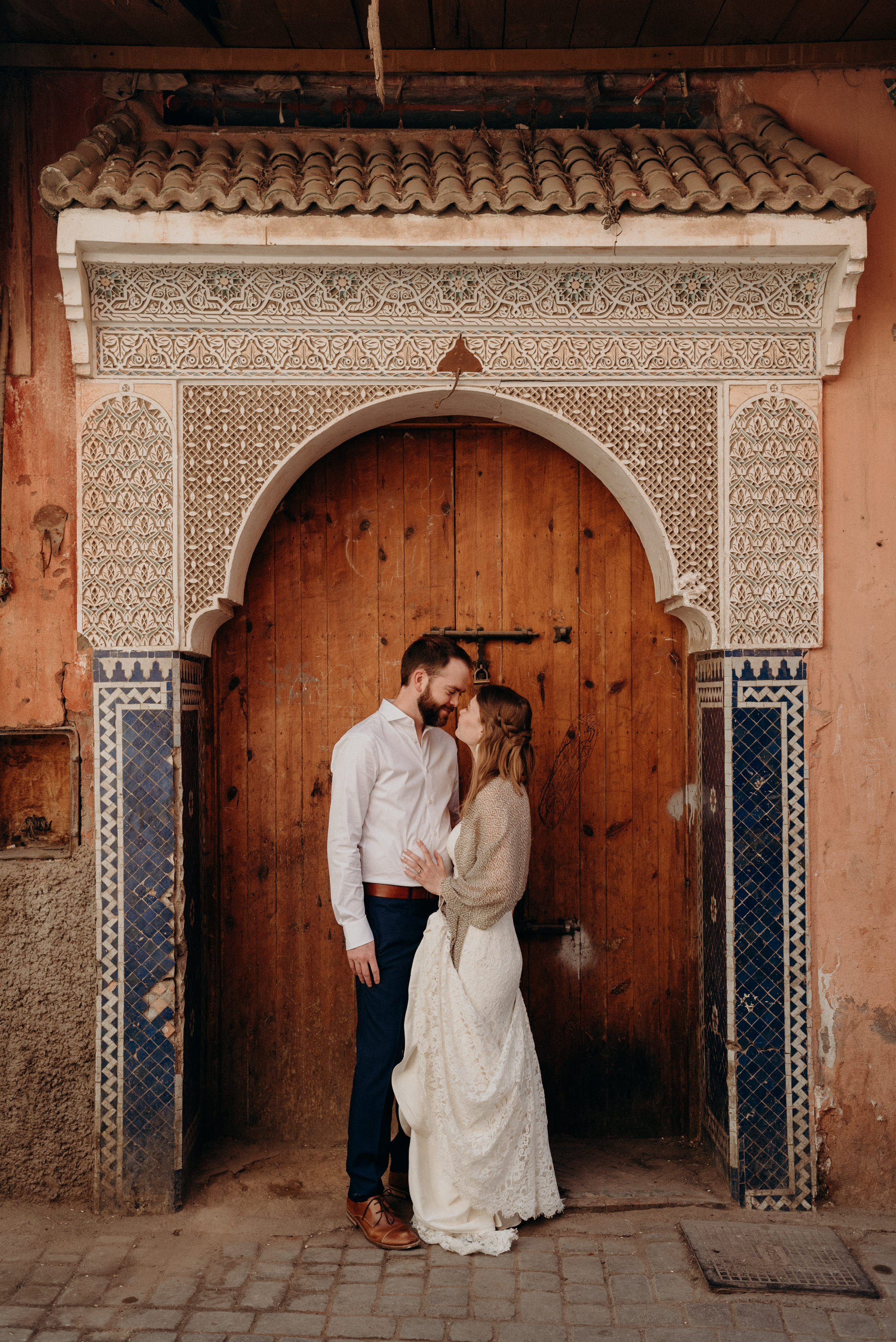 bride and groom standing in front of detailed doorway in Marrakech medina for elopement