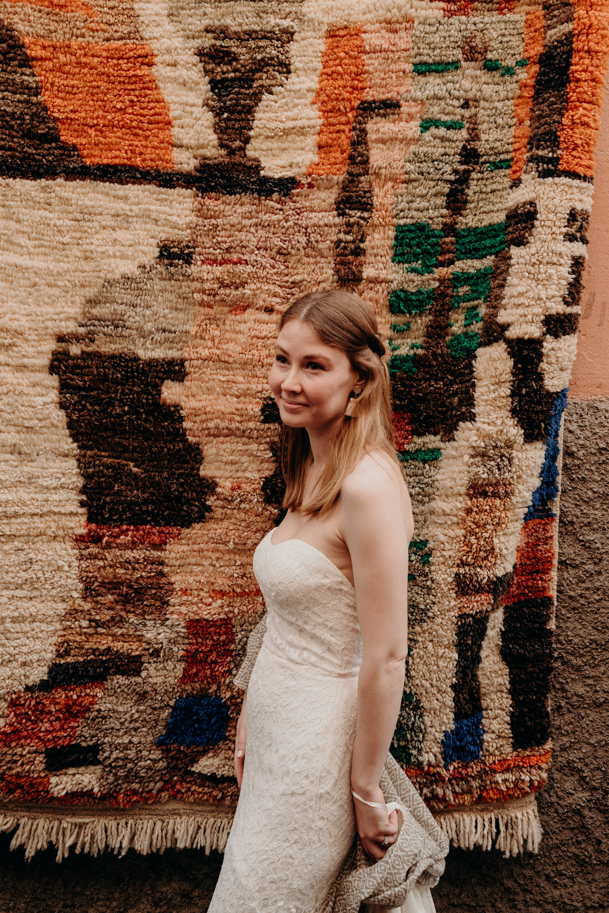 Bride standing in front of berber rug hanging in the medina in Marrakech