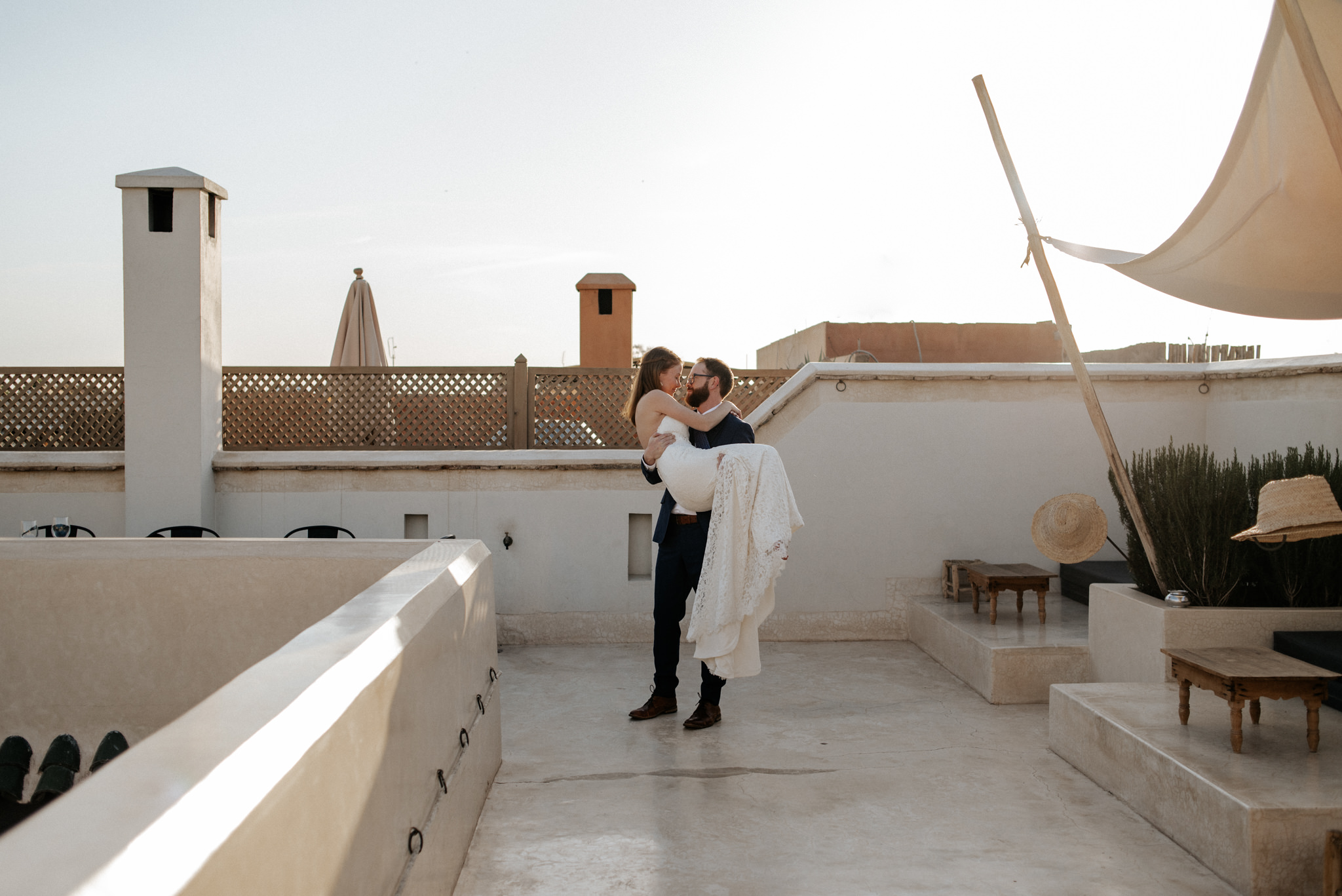Groom carrying bride on rooftop at sunset at Riad 42