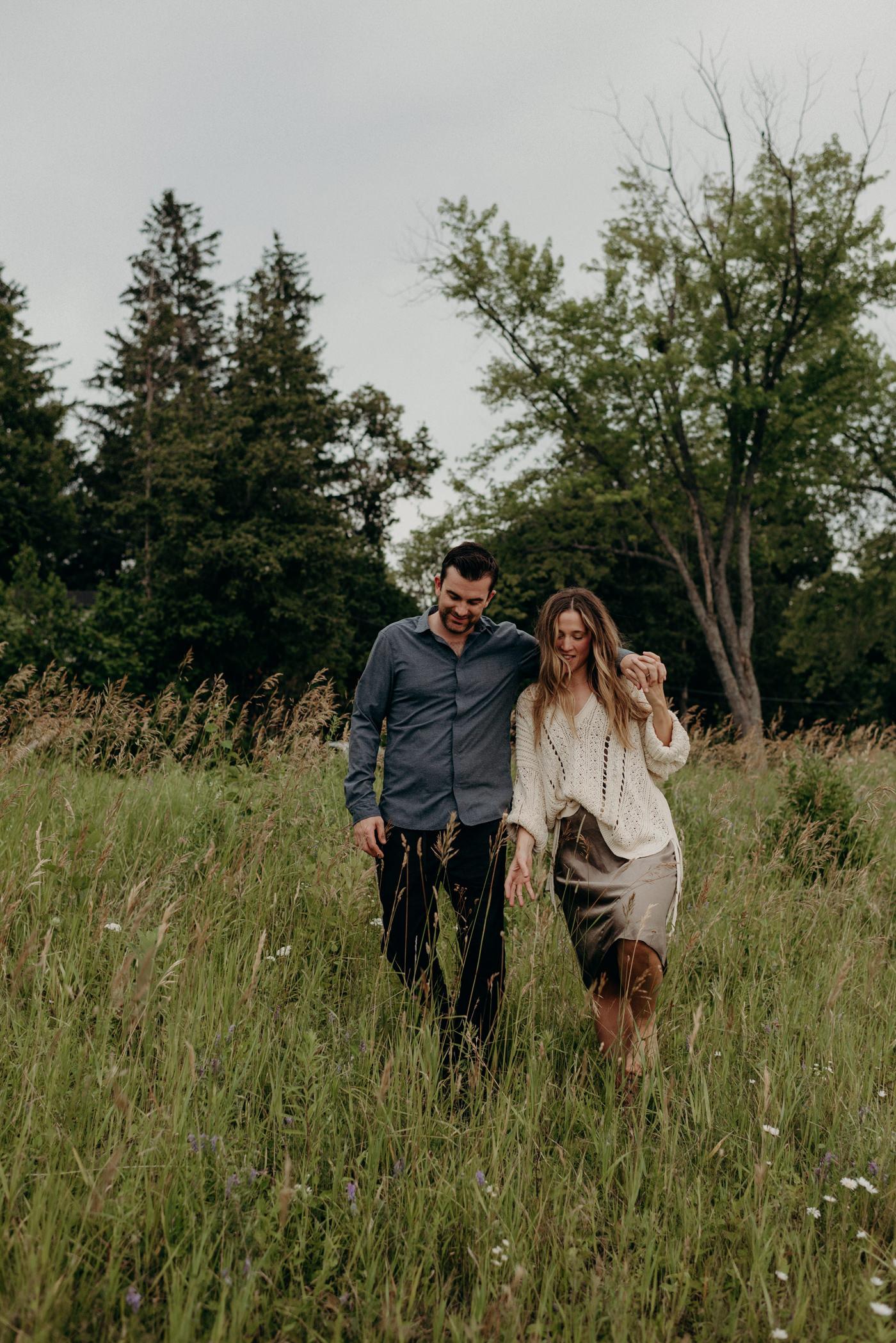 couple walking in field, holding hands