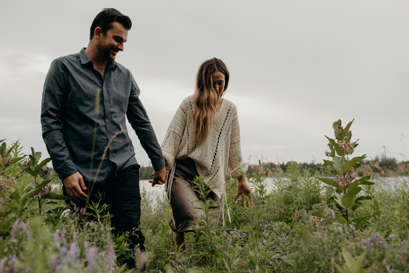 couple holding hands in tall grass