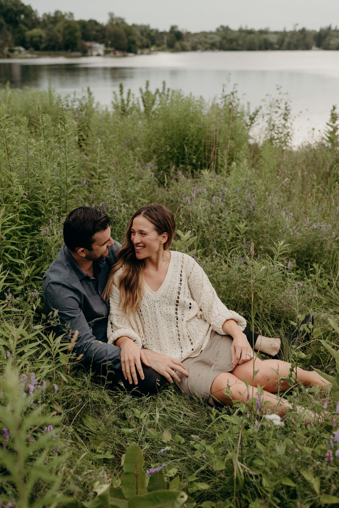 couple sitting in tall grass by lake