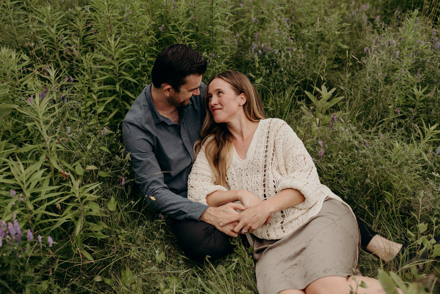 couple lying in tall grass cuddling