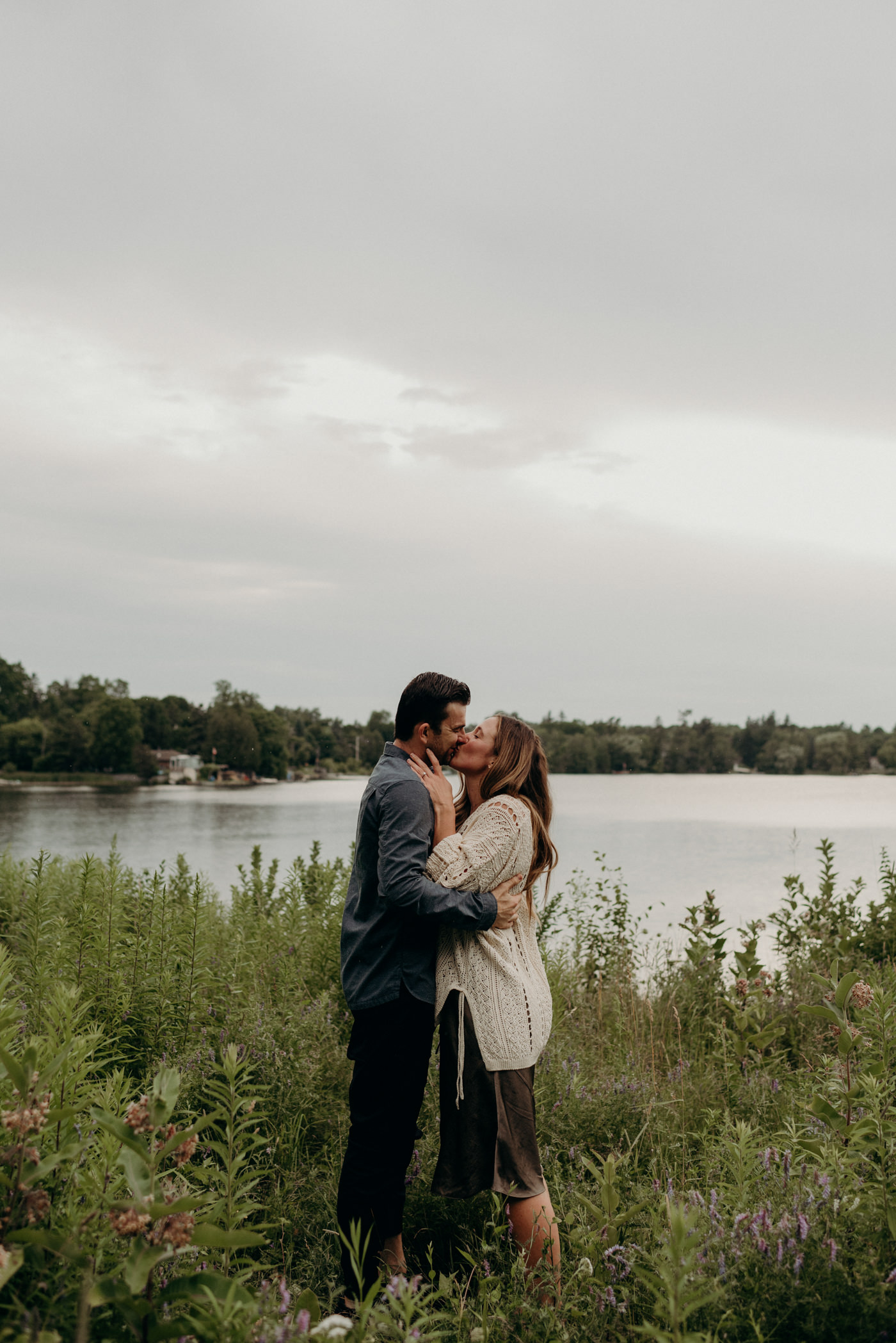 couple kissing in tall grass by lake