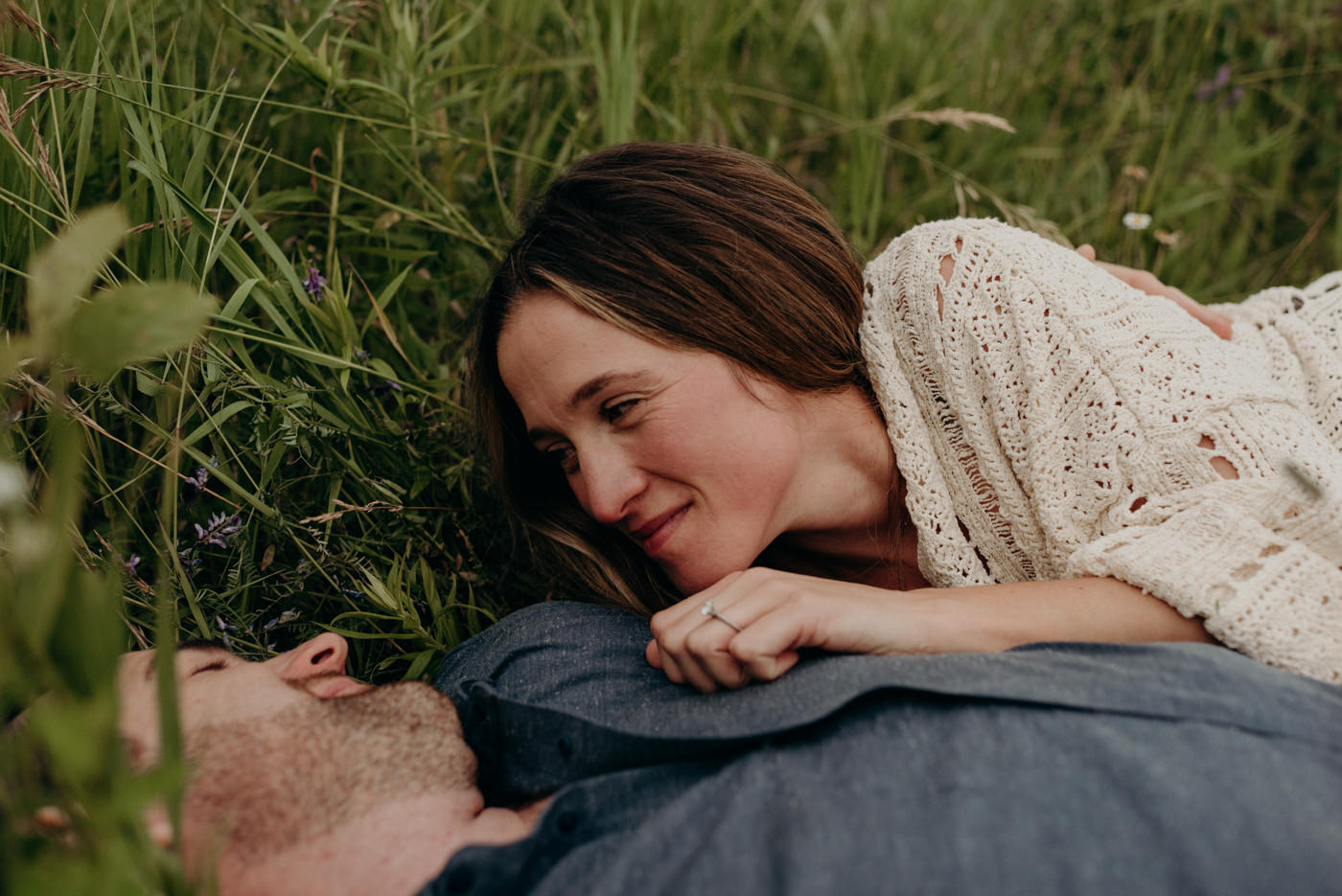 woman looking at man, lying in tall grass