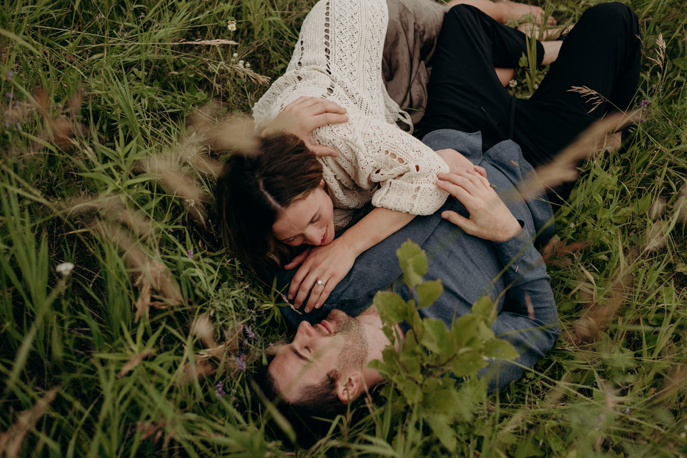 couple cuddling and lying down in tall grass