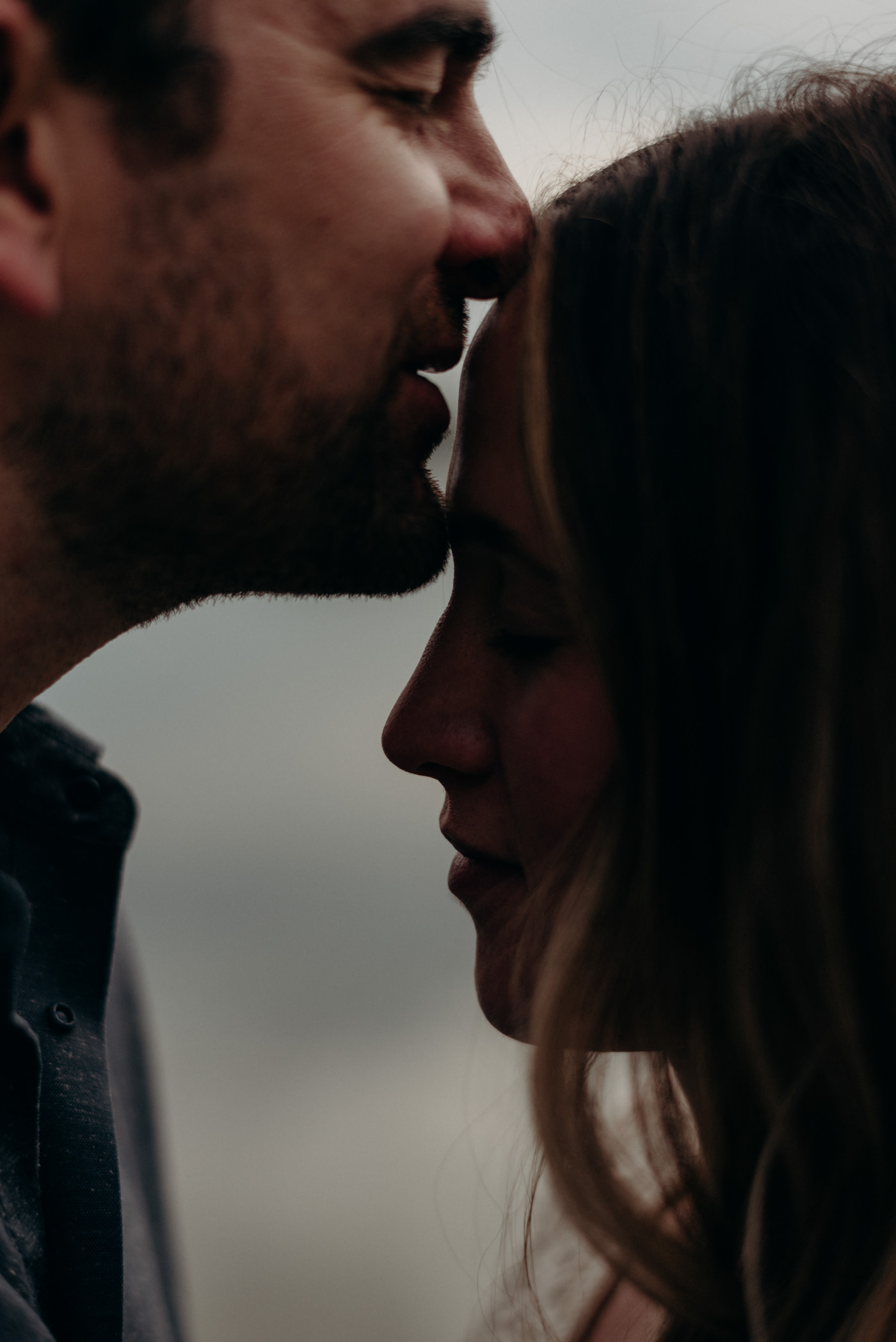 close up of man kissing woman on forehead