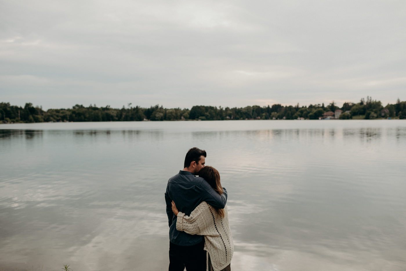 couple hugging by edge of lake