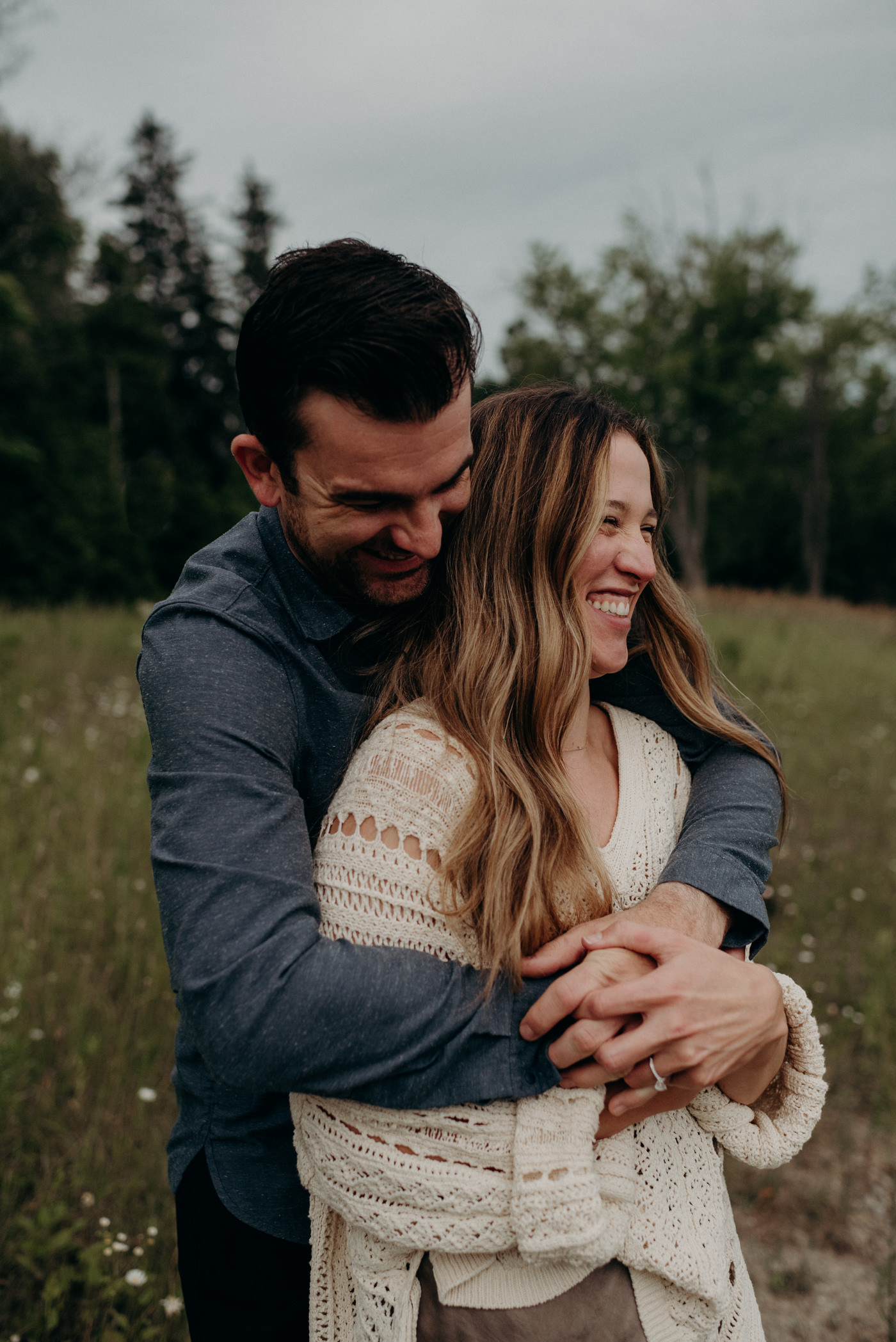 Couple hugging in field at dusk