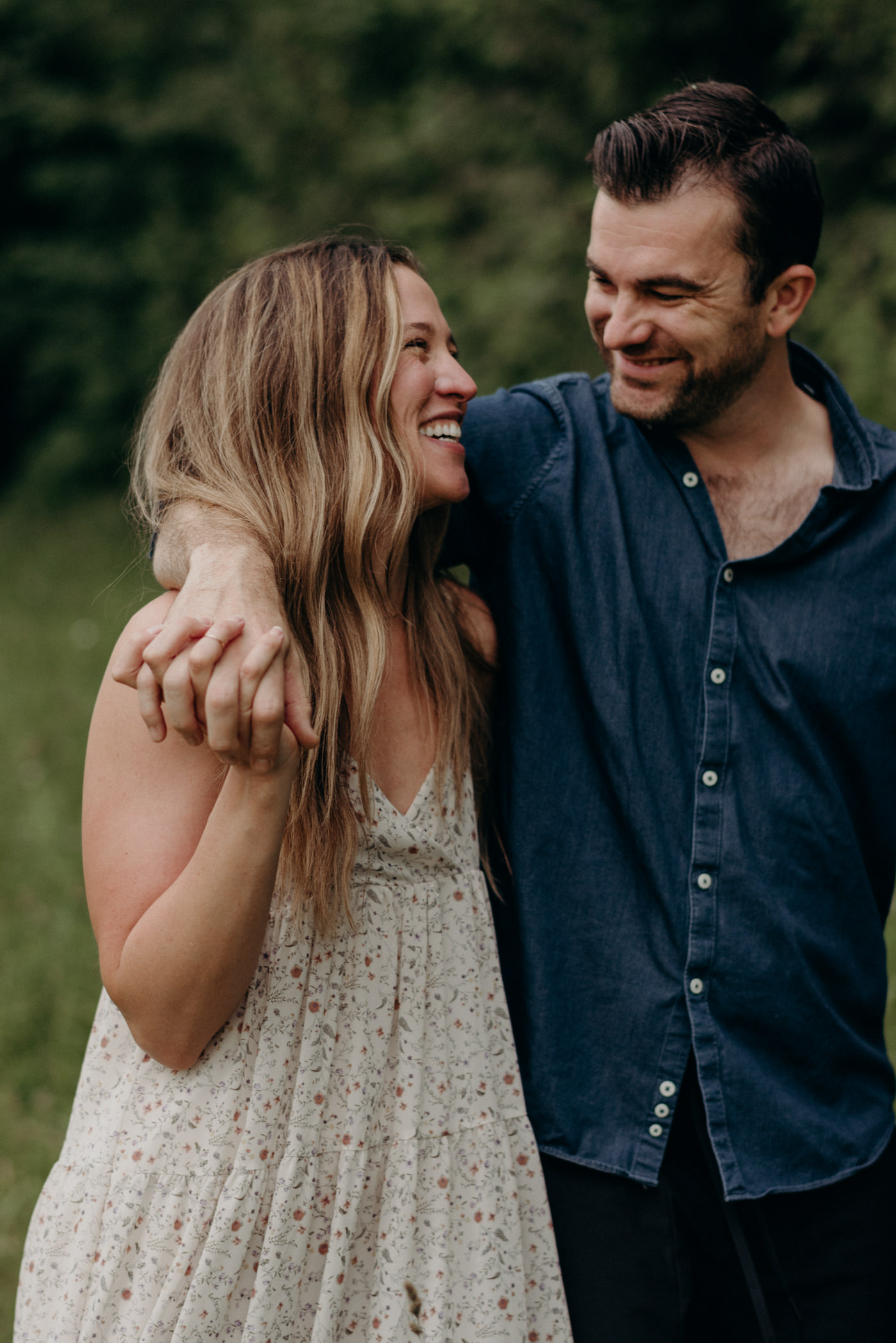 happy couple walking in field of tall grass and flowers for engagement shoot in Stouffville