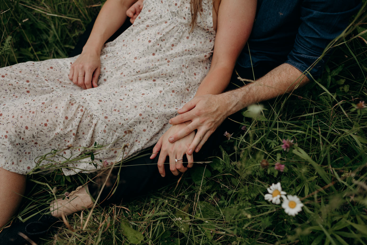 summer engagement shoot couple sitting in tall grass with flowers