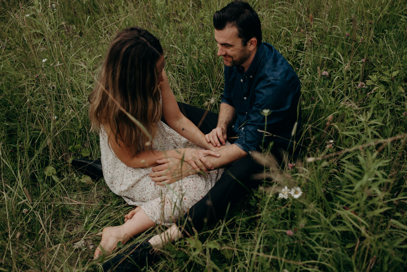 couple sitting in field of grass for engagement shoot
