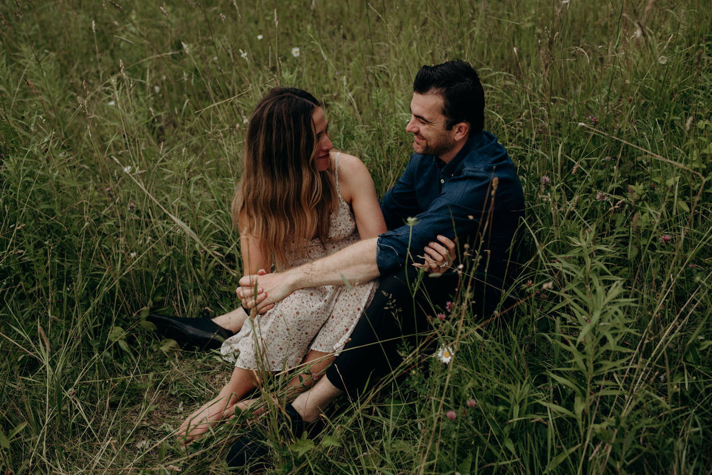 couple sitting in tall grass and looking at each other and smiling