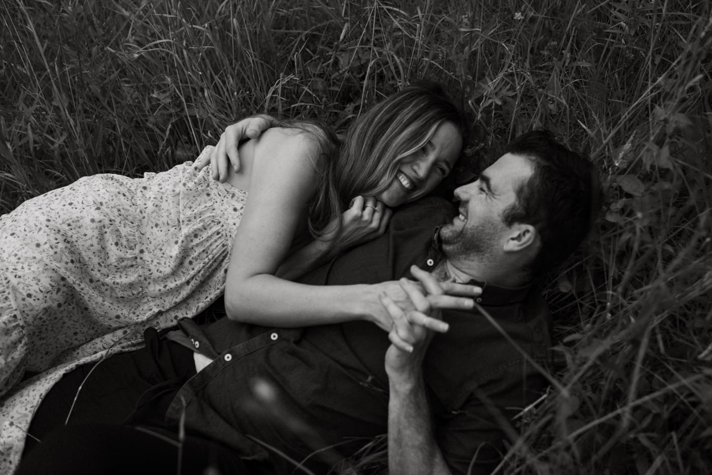 couple laughing and holding hands as they roll in tall grass