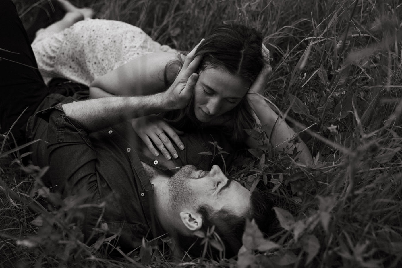 couple lying in tall grass, man gently holding woman's face