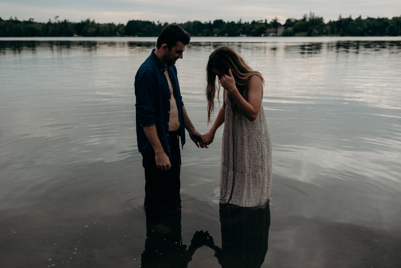 couple holding hands and standing in water at lake