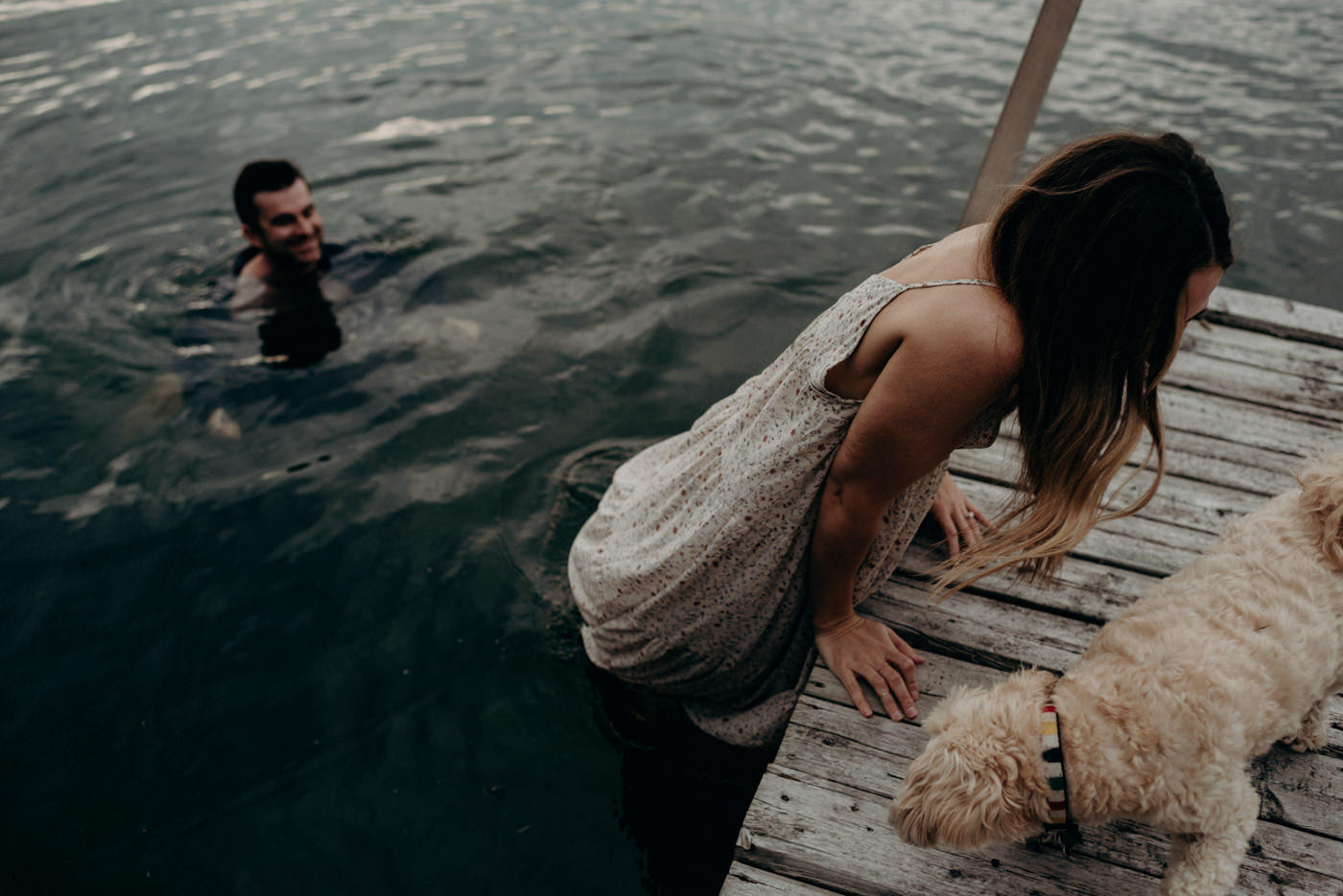 woman jumping into lake from dock for their warm summer night engagement shoot