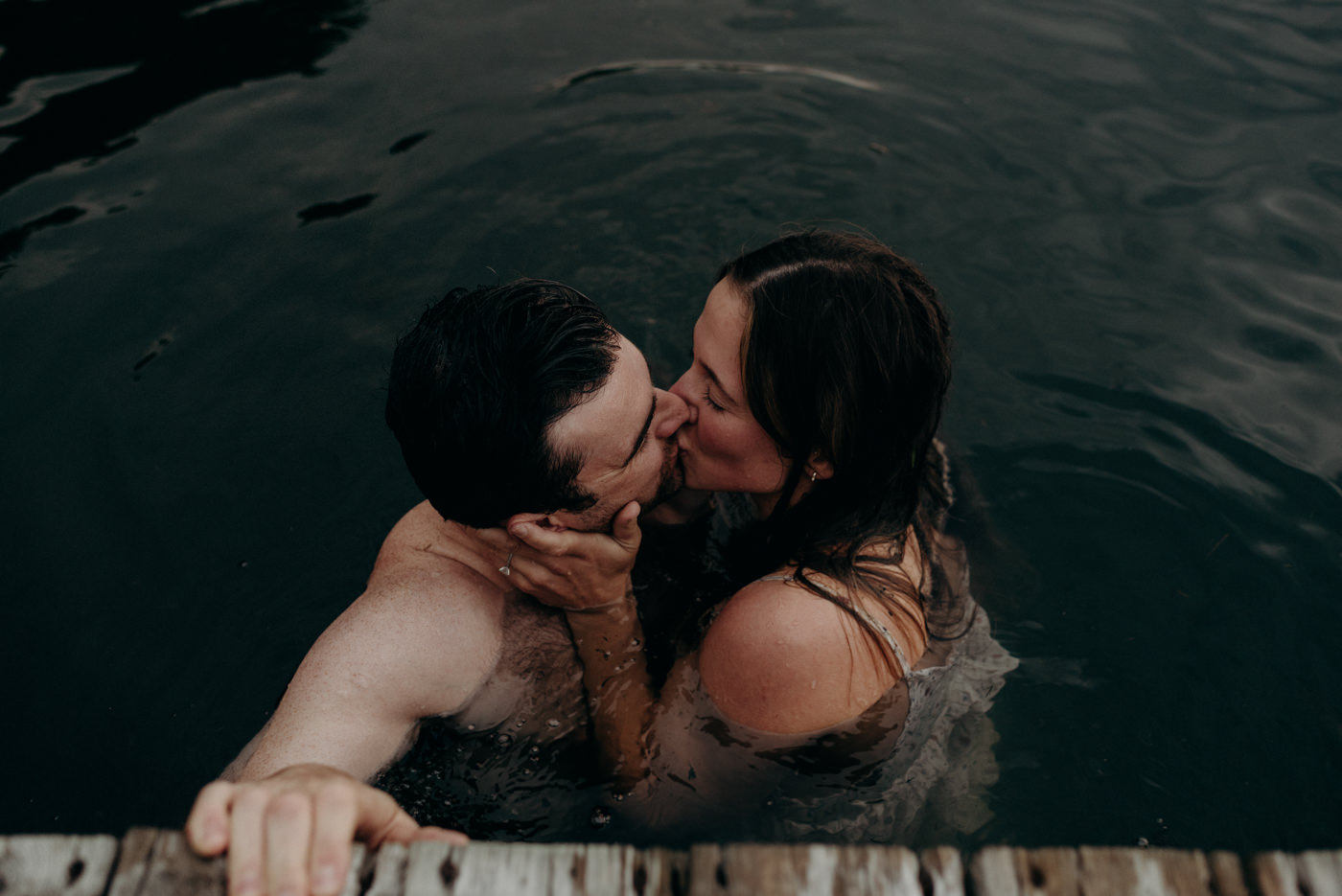 couple kissing in water holding onto dock for their warm summer night engagement