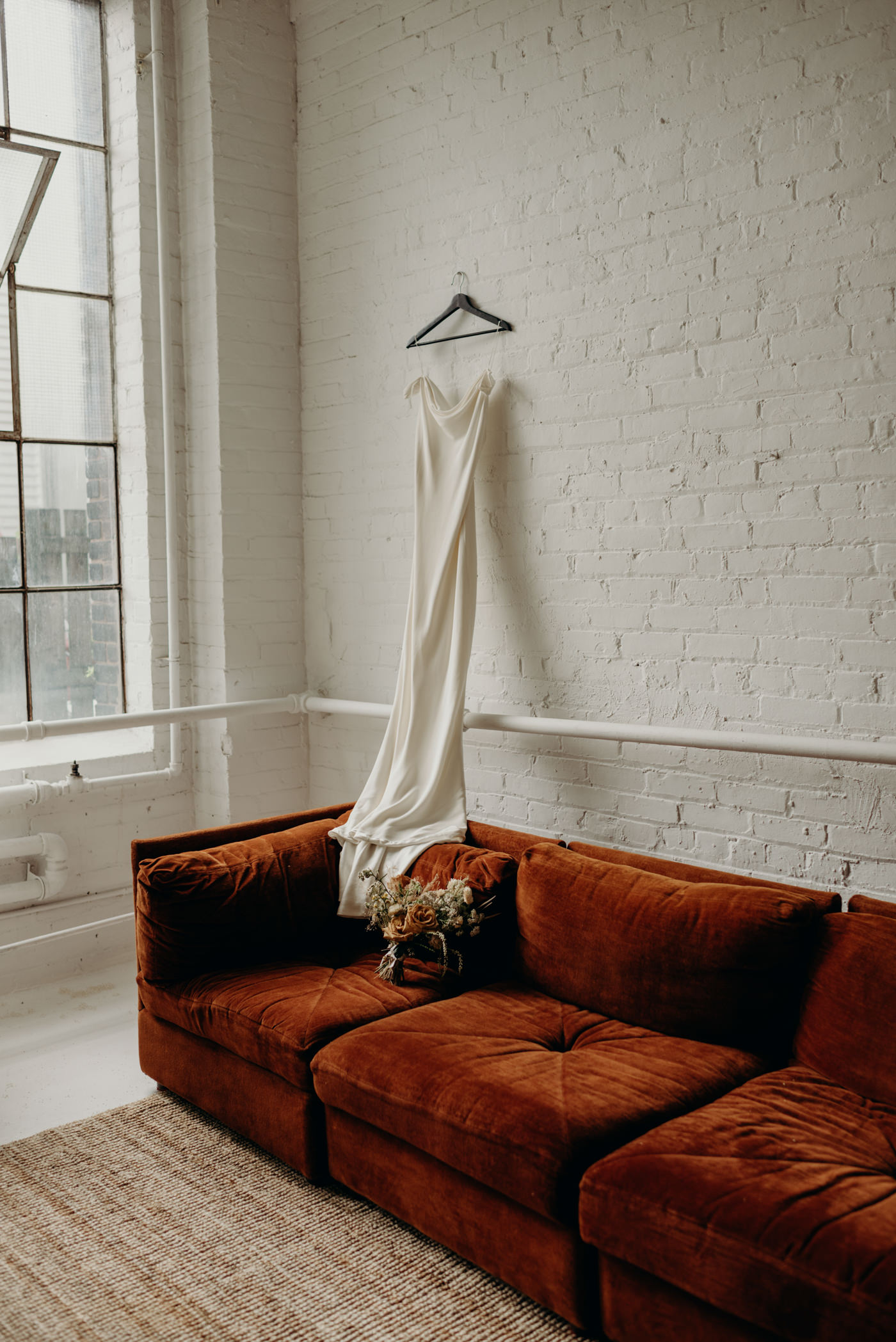 wedding dress hanging on white brick wall with flowers on velvet couch