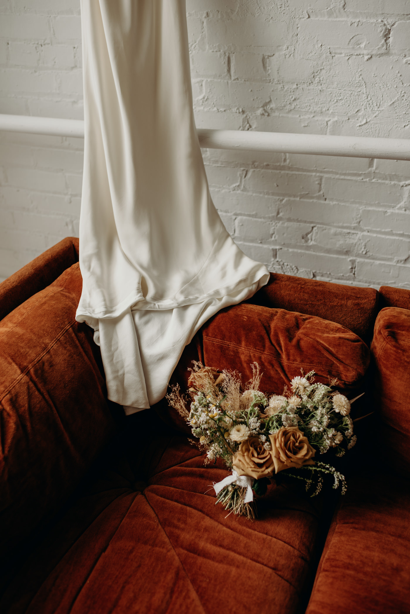 wedding dress draped over burnt orange velvet couch with dried floral bouquet