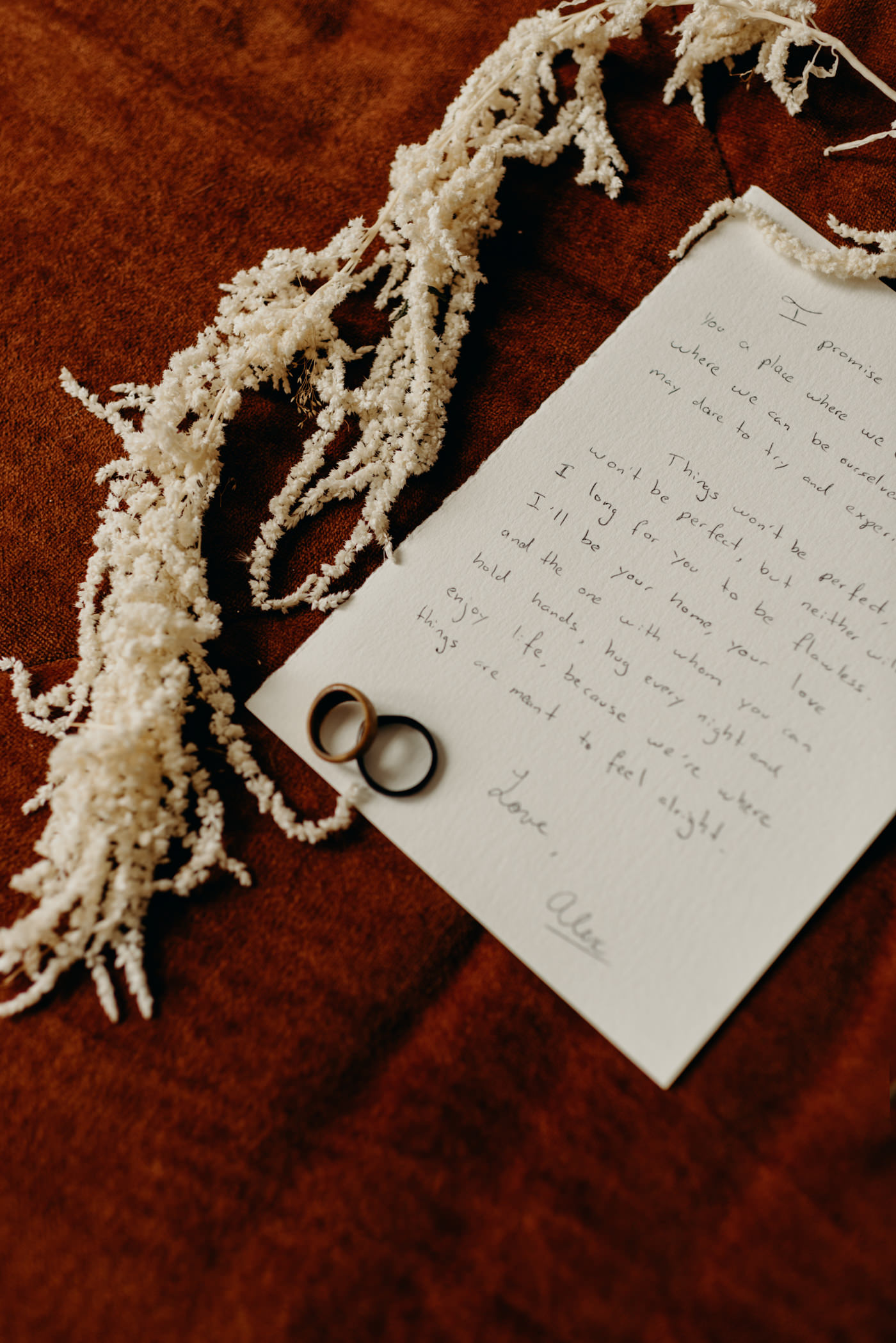 handwritten vows on orange velvet touch with rings
