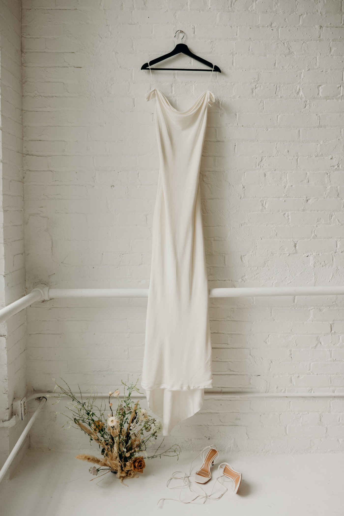 Savannah Miller Bridal wedding dress hanging on white brick wall with florals on ground
