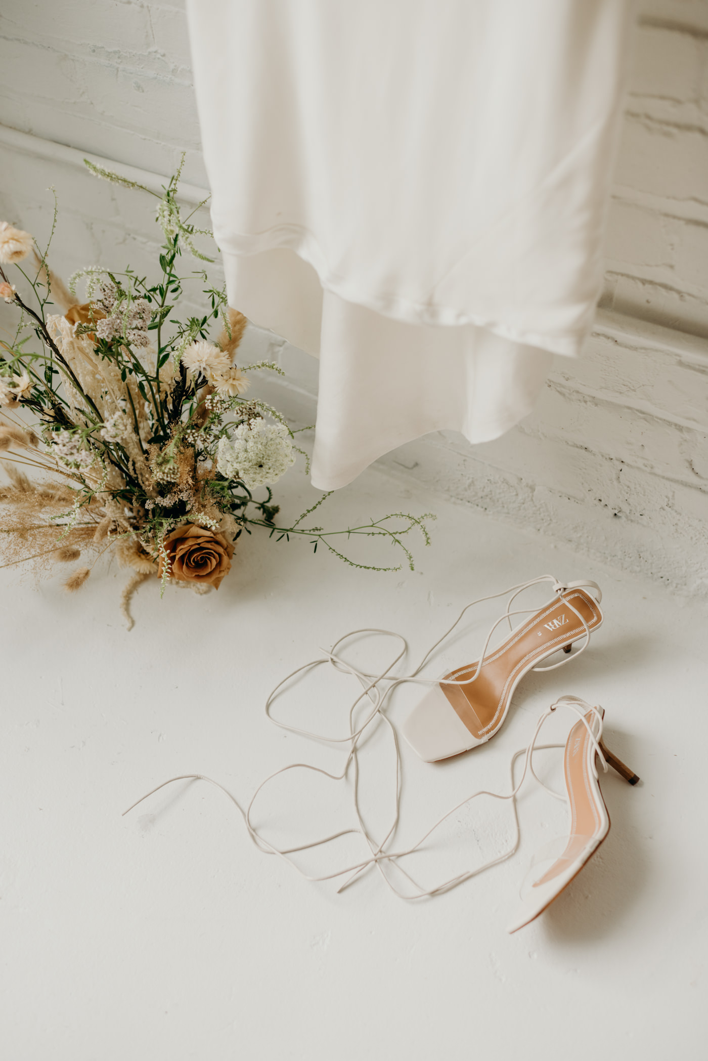 white wedding details and bride accessories on white loft floor