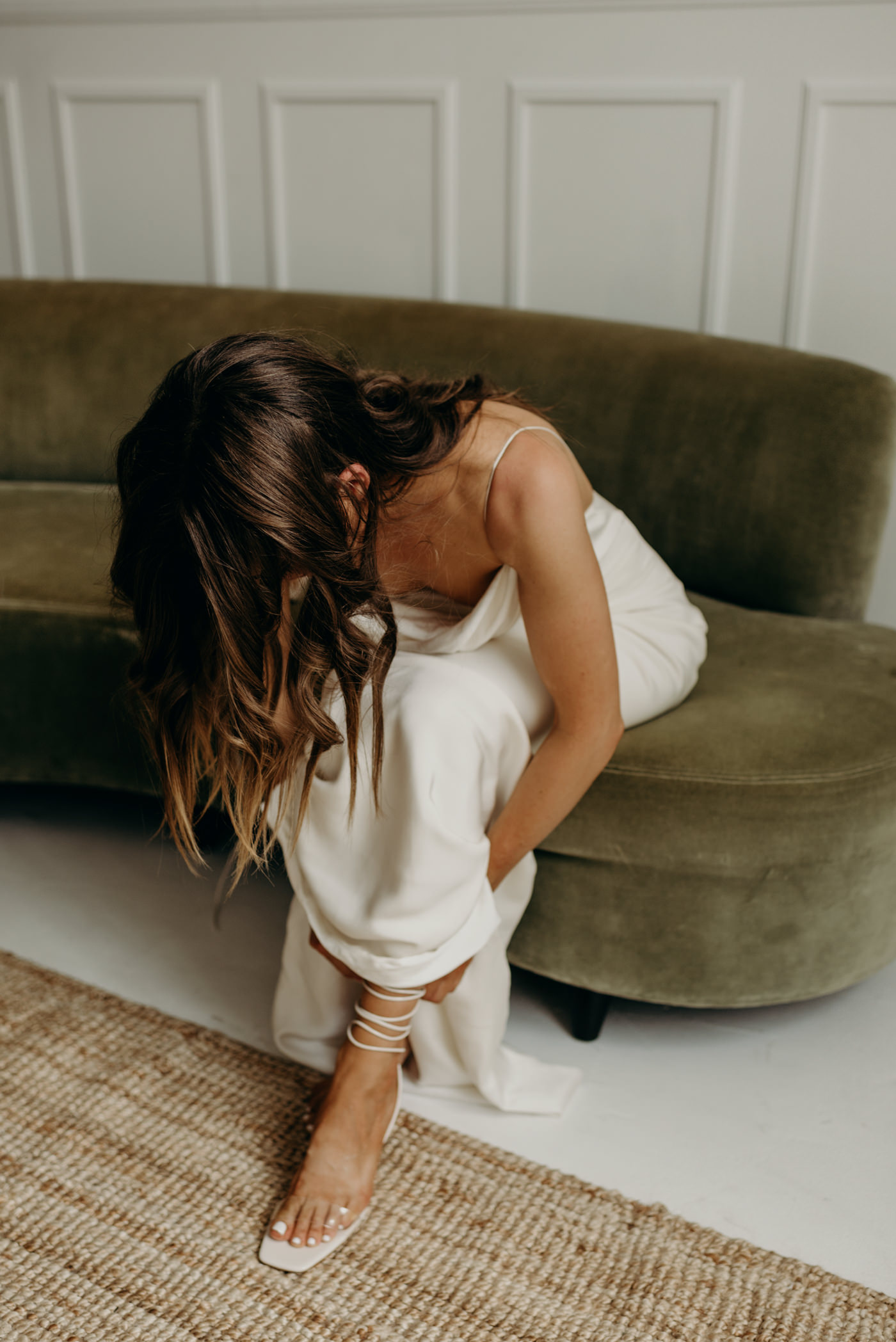 bride tying up shoes while sitting on velvet couch in cool midcentury loft elopement