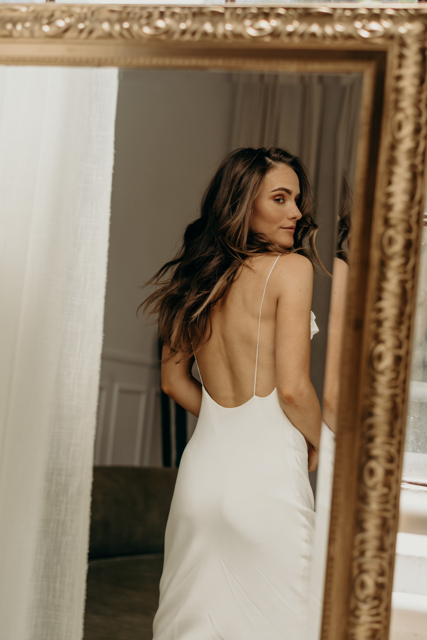 bride checking out back of dress in mirror reflection