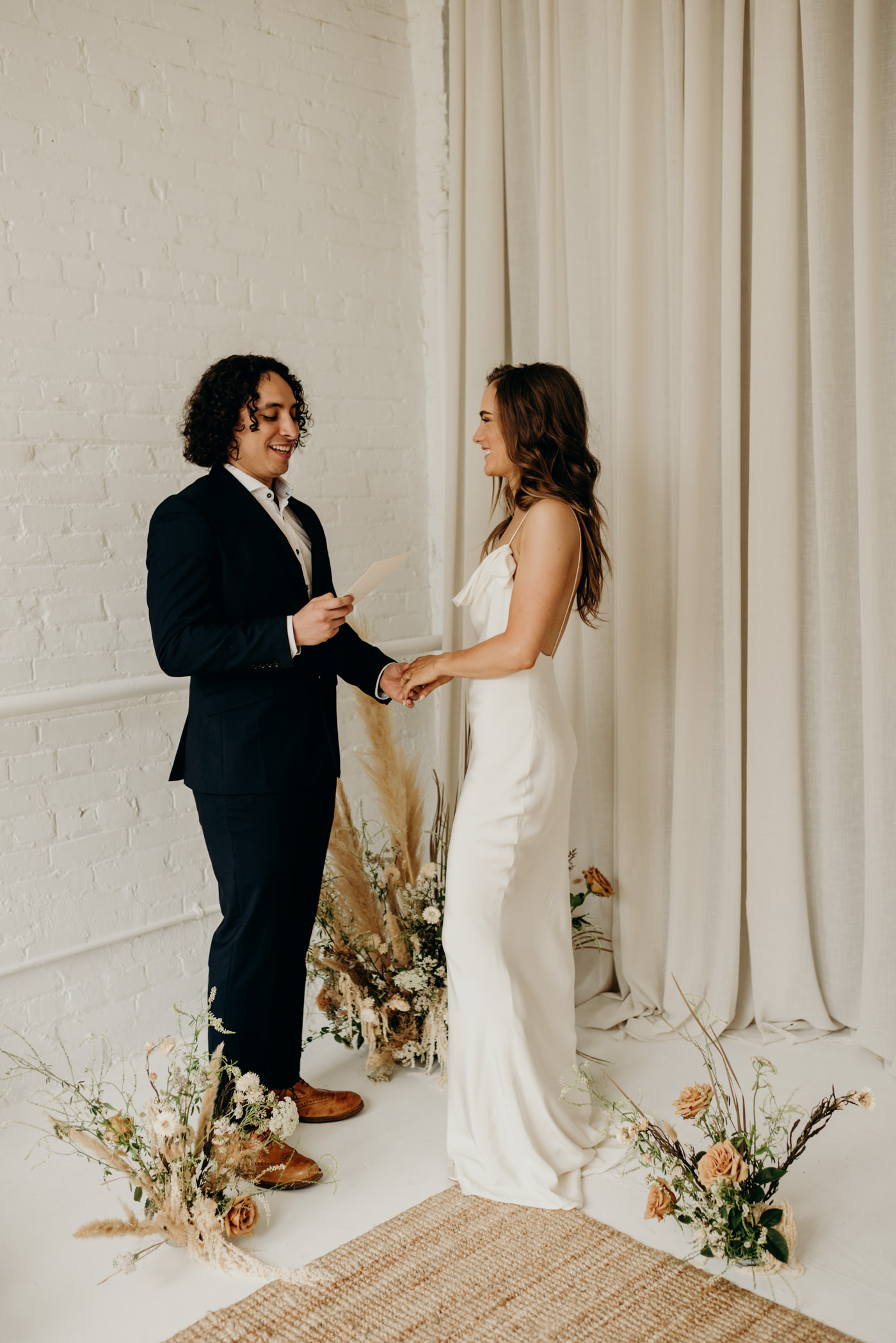 bride and groom holding hands as groom reads vows in cool midcentury loft elopement at Lovt Studio East in Toronto