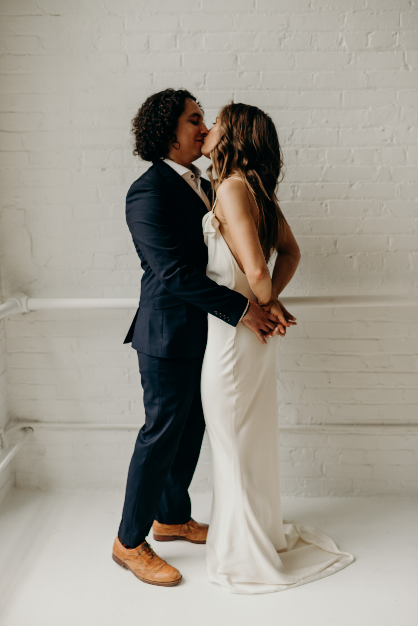 bride and groom hugging and kissing in white brick was hard loft in Toronto