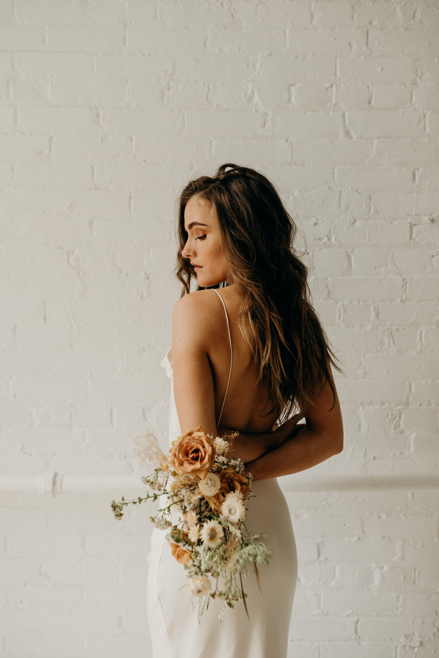 Bride in white brick wall loft wearing Savannah Miller bridal and orange dried flower bouquet