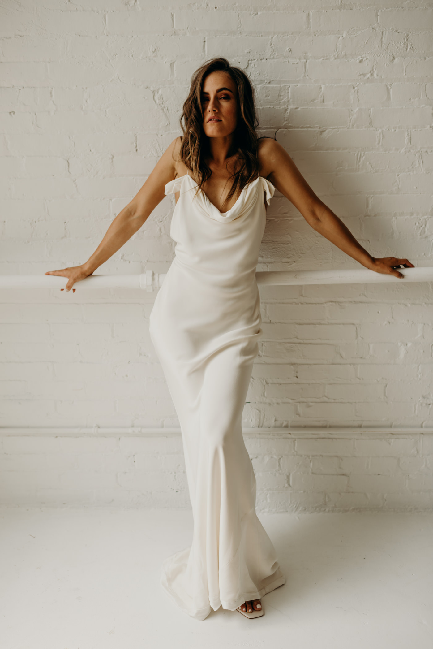 Bride in white brick wall hard loft wearing Savannah Miller bridal gown
