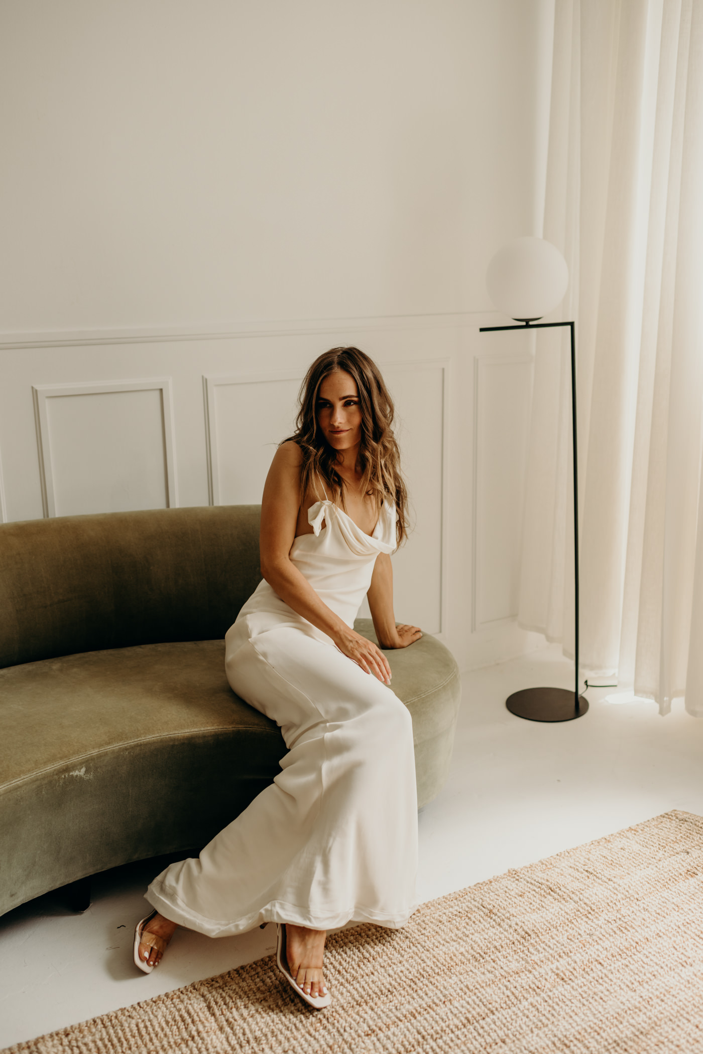 bride on green velvet couch wearing Savannah Miller bridal