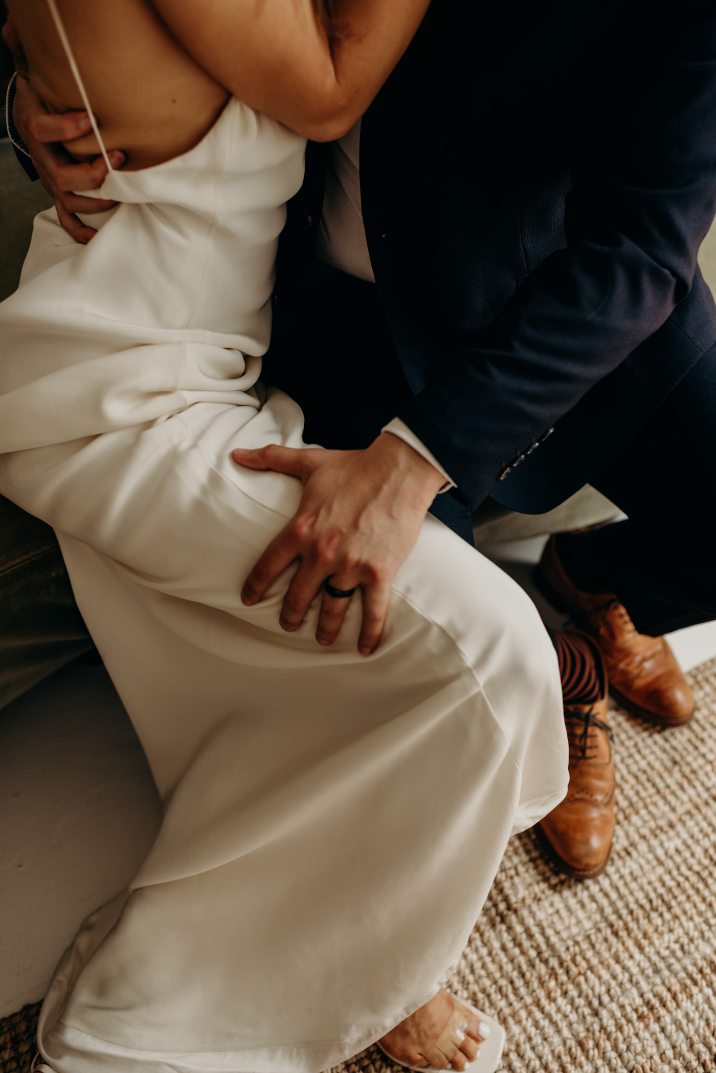 groom hand on brides leg as they kiss