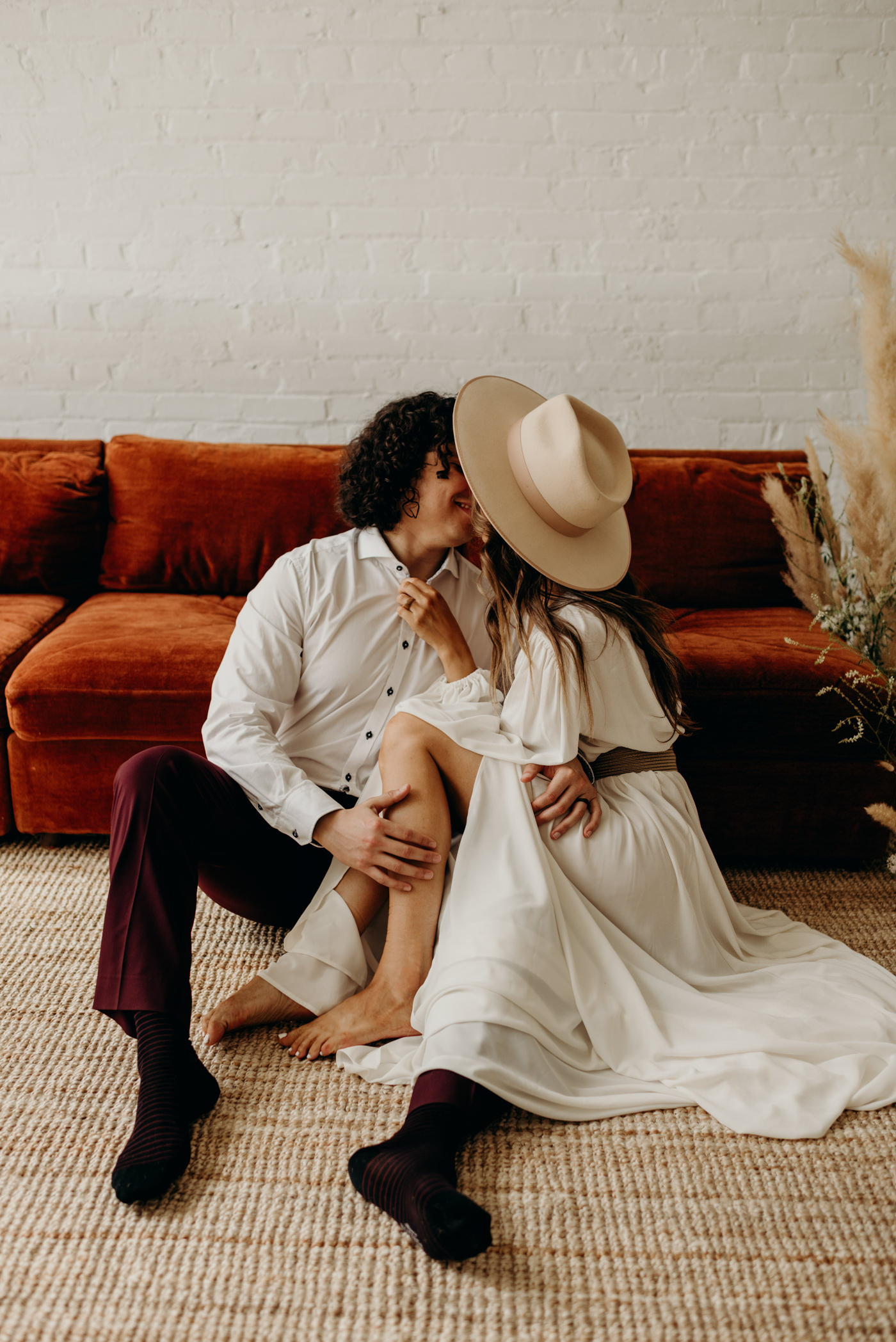 bohemian couple sitting on floor of loft kissing