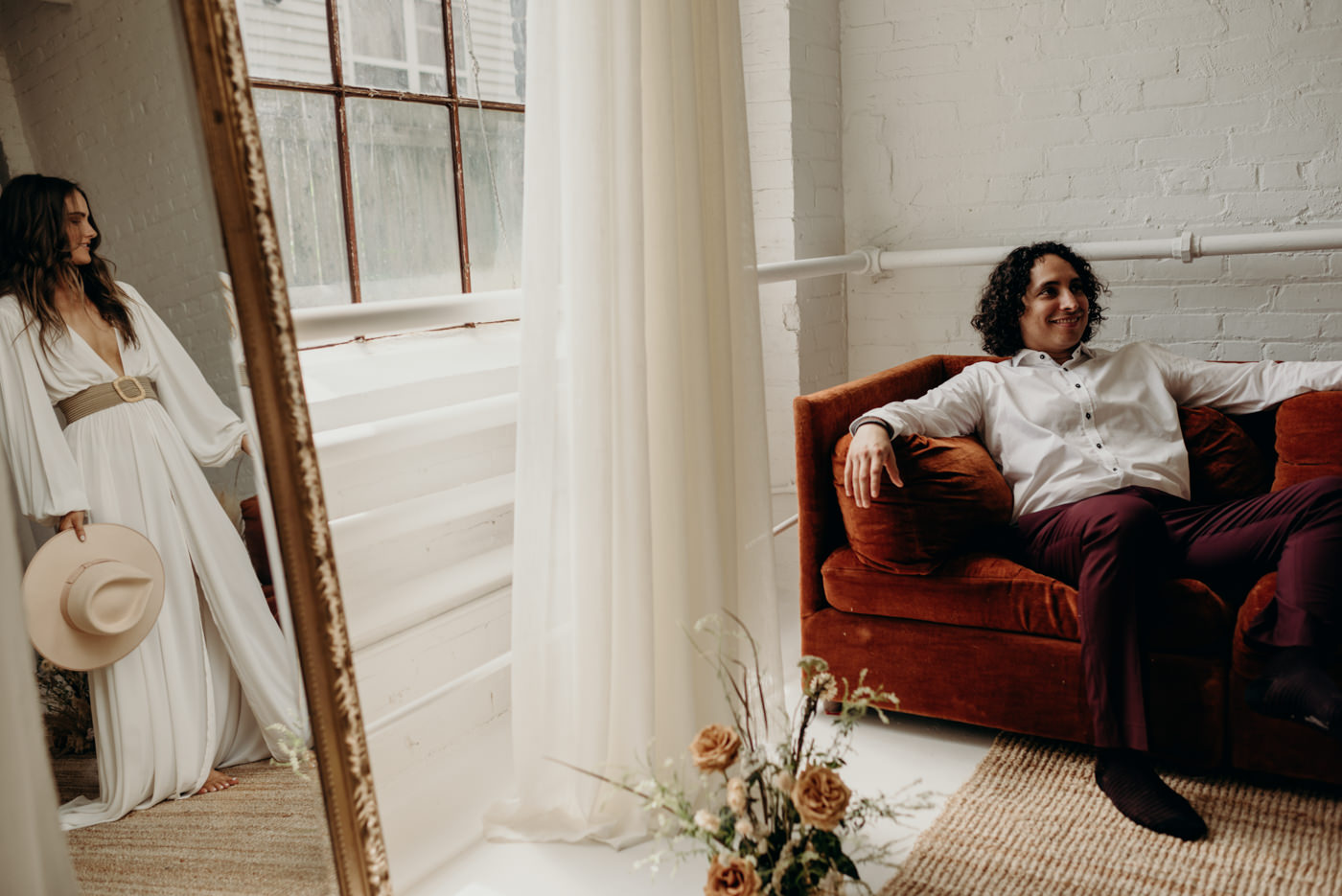 cool wedding portrait of groom sitting on orange velvet couch and reflection of bride looking at him