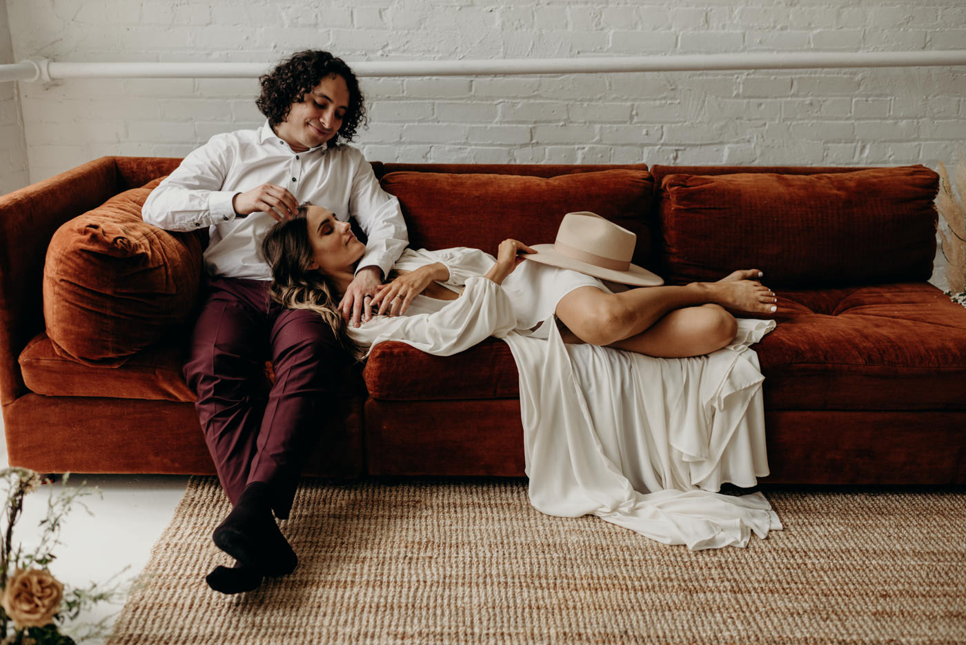 bride lying down on grooms lap on velvet couch in cool midcentury loft elopement in Toronto