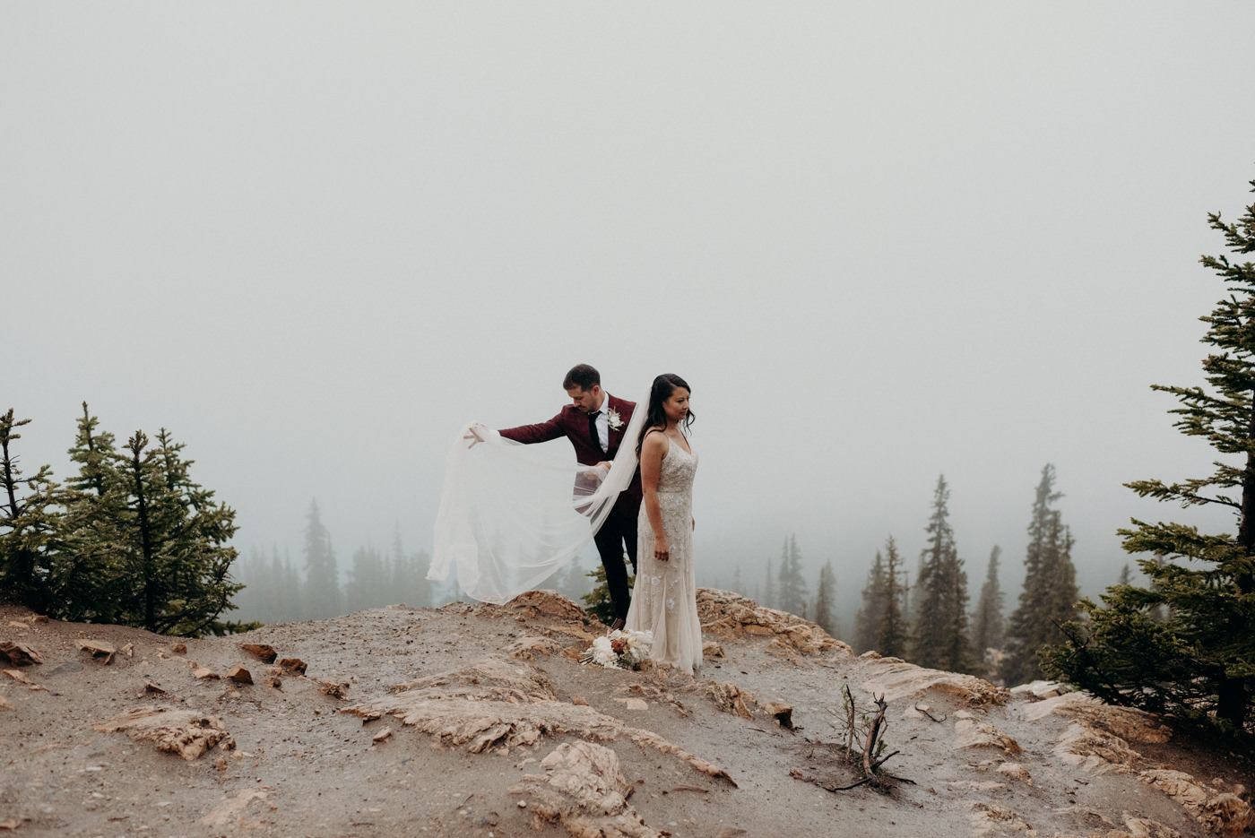 groom helping bride with veil in a foggy mountain side
