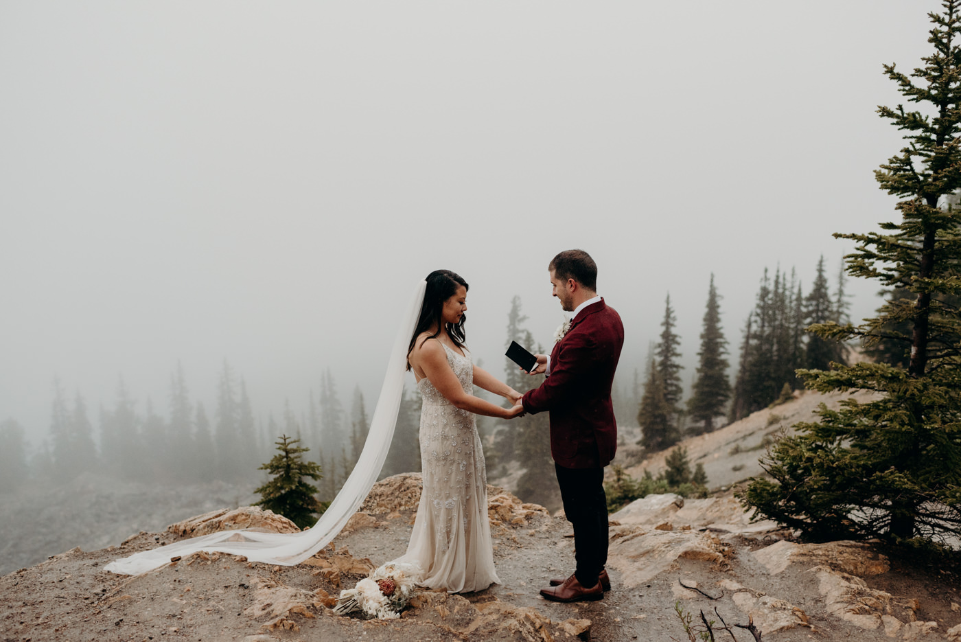 groom reading vows in the rain on a foggy mountainside in Banff