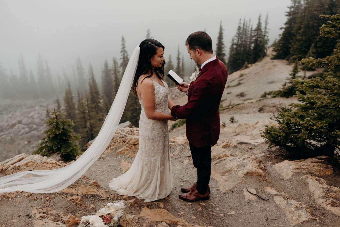 groom reads vows to bride on a rainy morning in Banff National Park